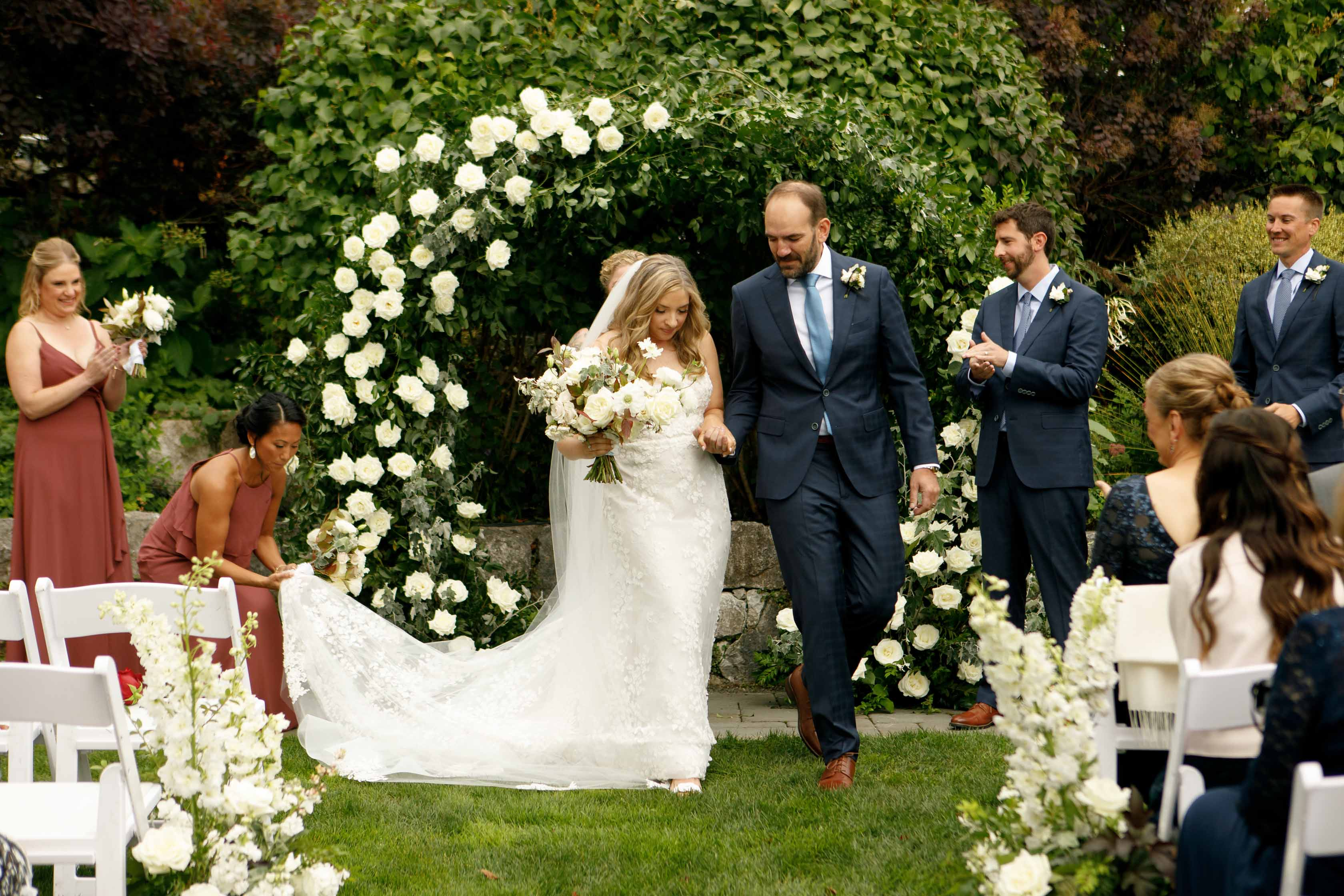 Dawn and Ben just married, wedding couple in front of circle arche with greenery and white roses - designed by  Flora Nova Design