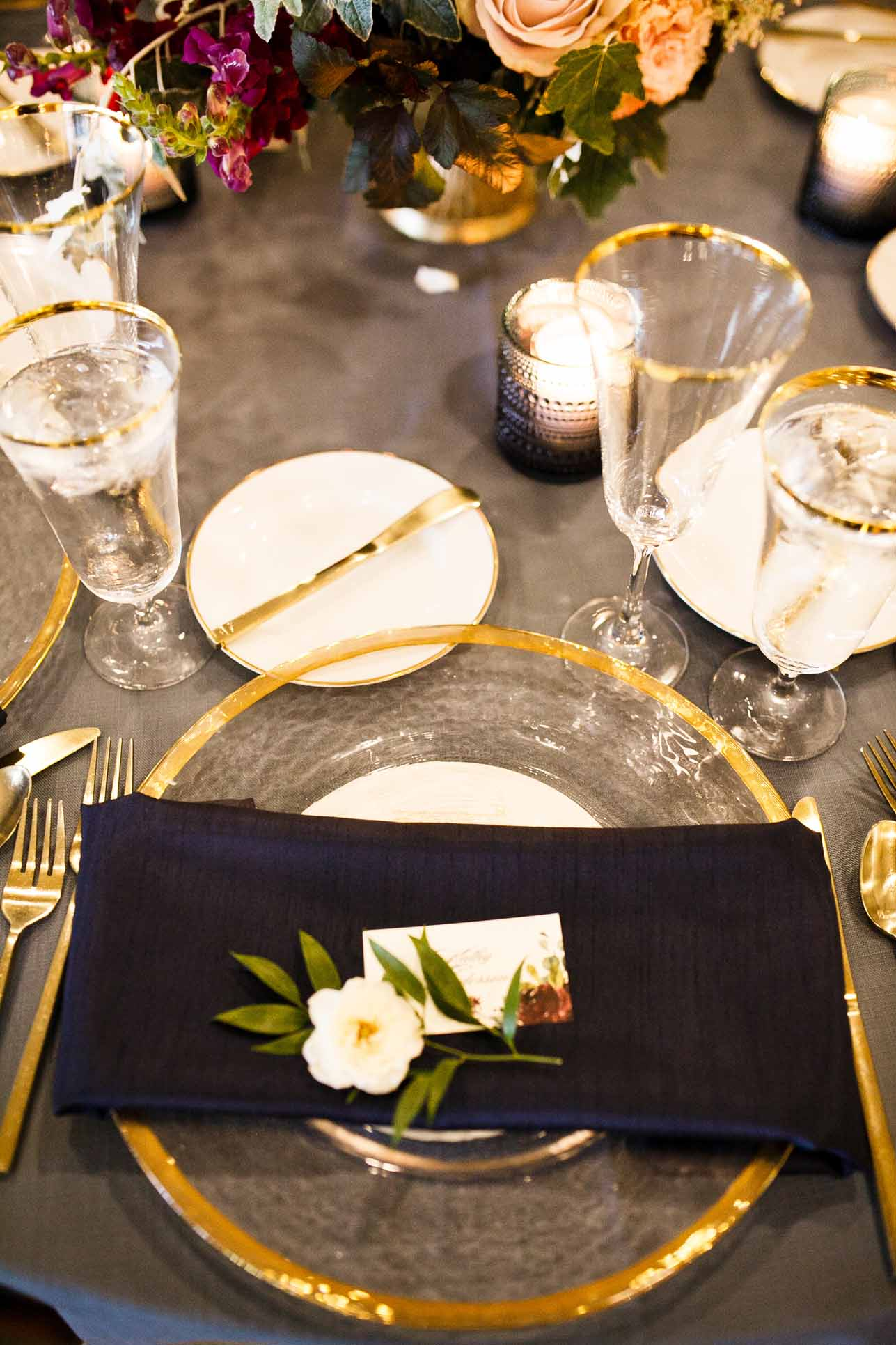 Table setting with navy napkin and gold rimmed glass charger plate