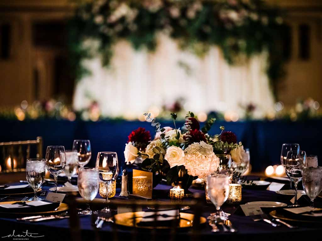 Wedding centerpiece in burgundy, blush, and cream on navy linens