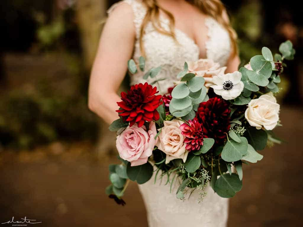 Bridal bouquet with burgundy dahlias, blush roses, panda anemones, and spiral eucalyptus