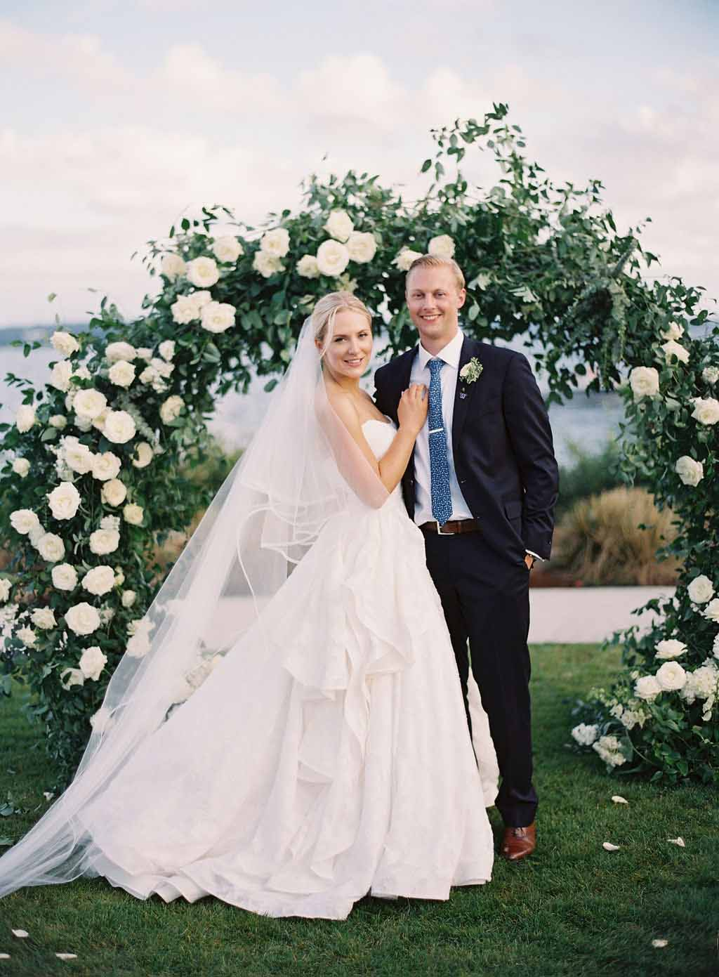 bride and groom pose in front of a tunnel arch decorated with greenery and white roses