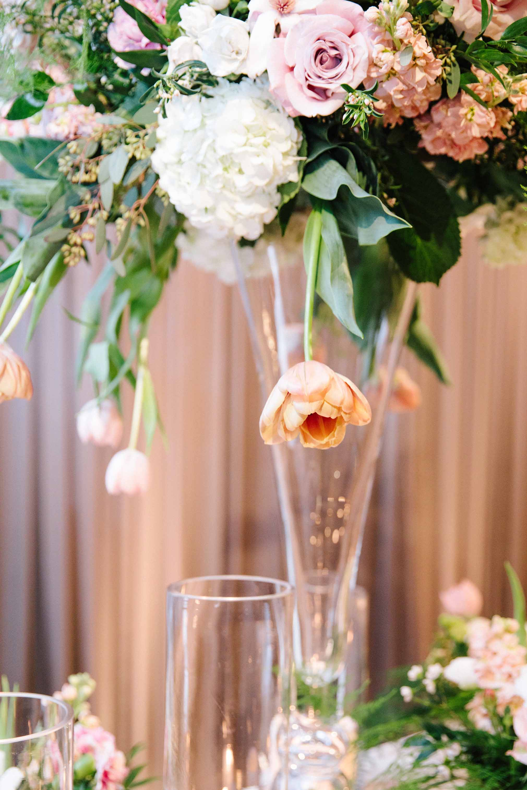 Detail shot of a draping peach tulips in a tall centepriece set on a crystal vase