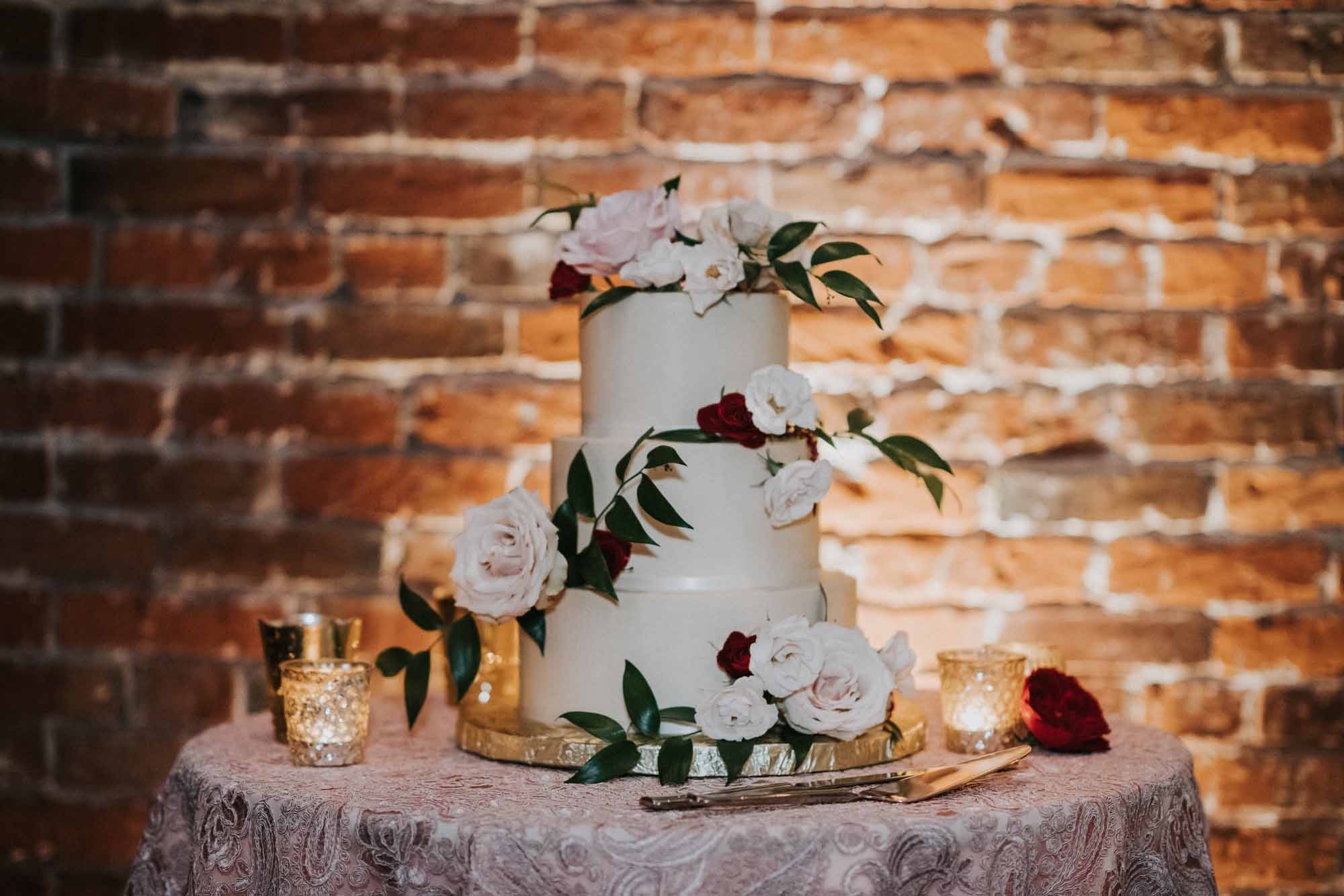 three tiered wedding cake decorated with roses