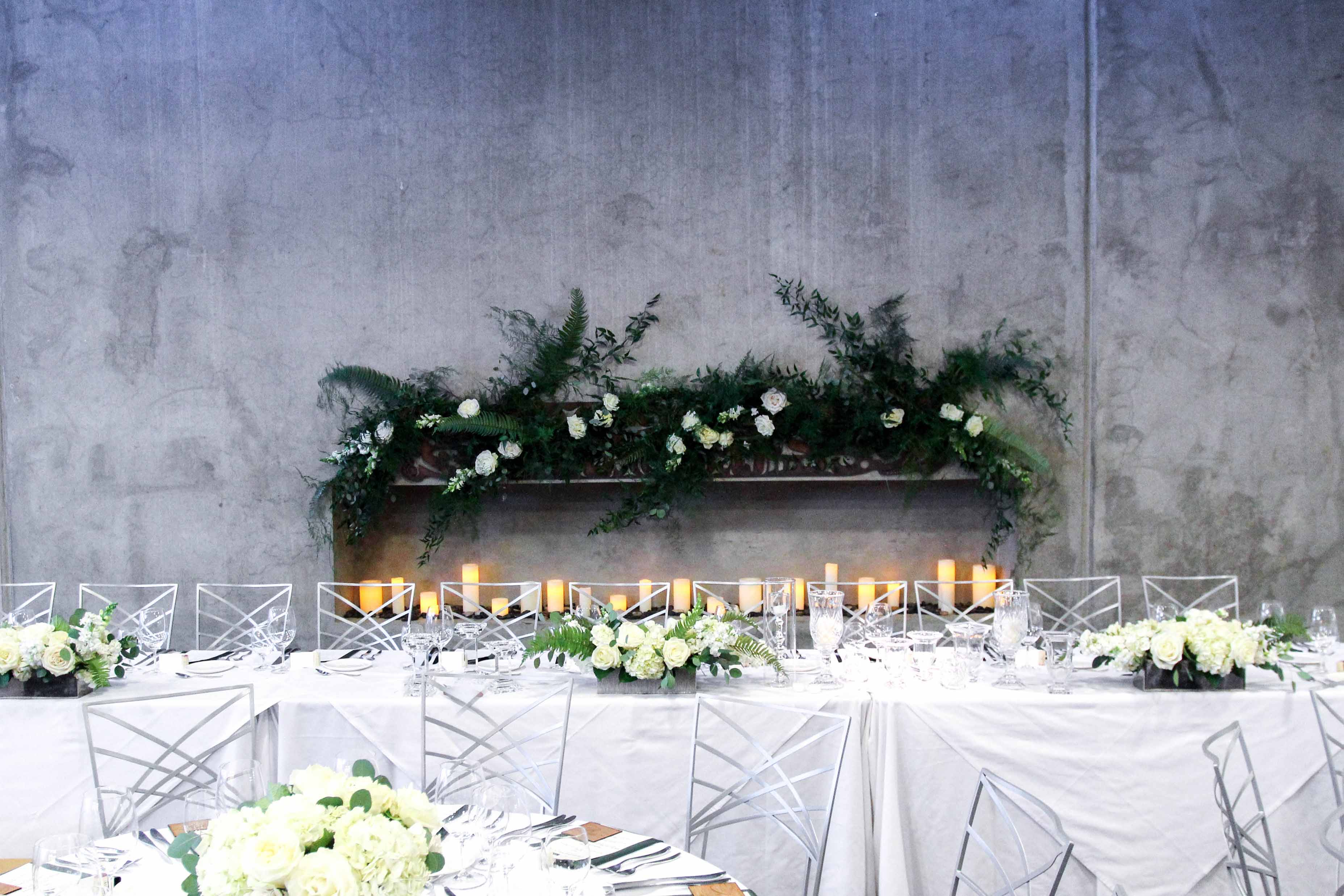 head table in front of candles and greenery installation on cement wall