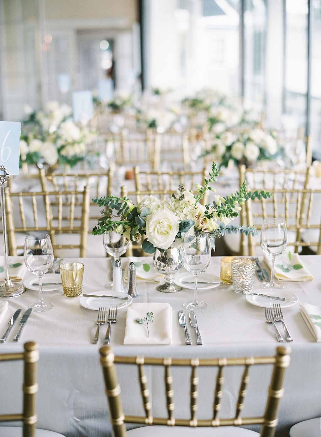 long tables at the reception of a seattle tennis club wedding decorated with white linens and compote arrangements