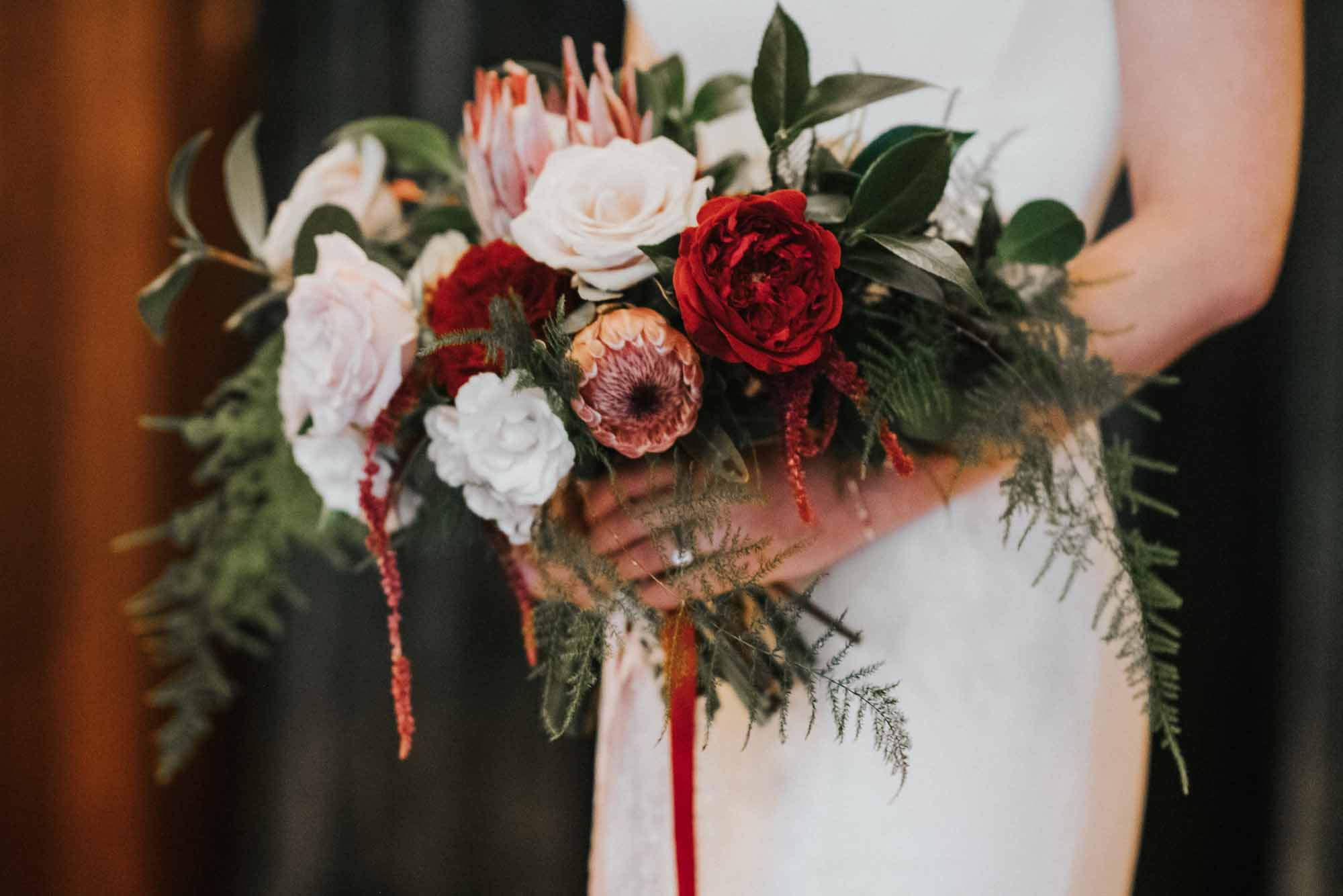 cozy winter wedding bouquet with protea, roses, amaranthus, and greens
