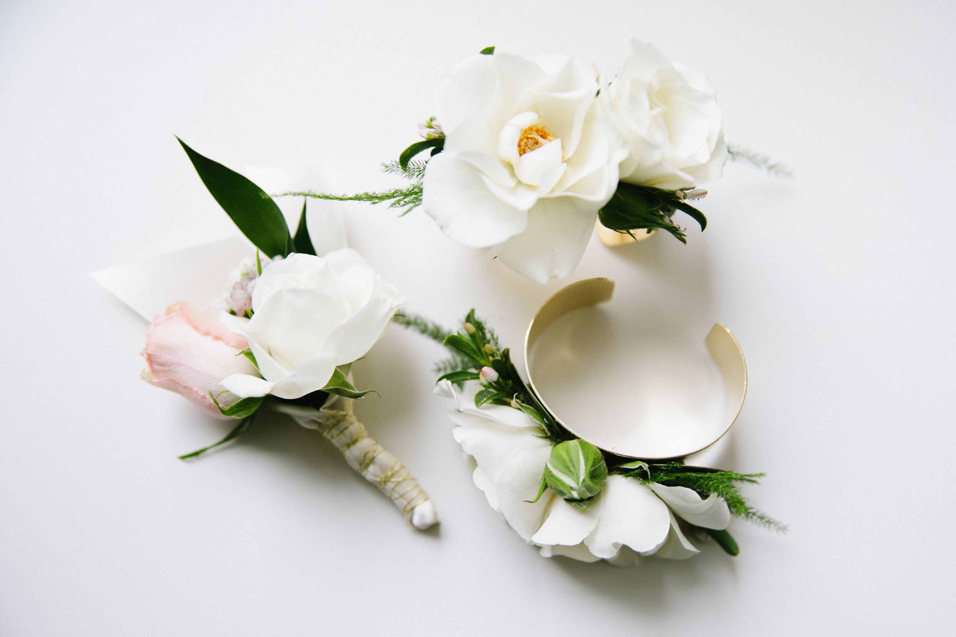 White floral boutonniere and two wrist corsages