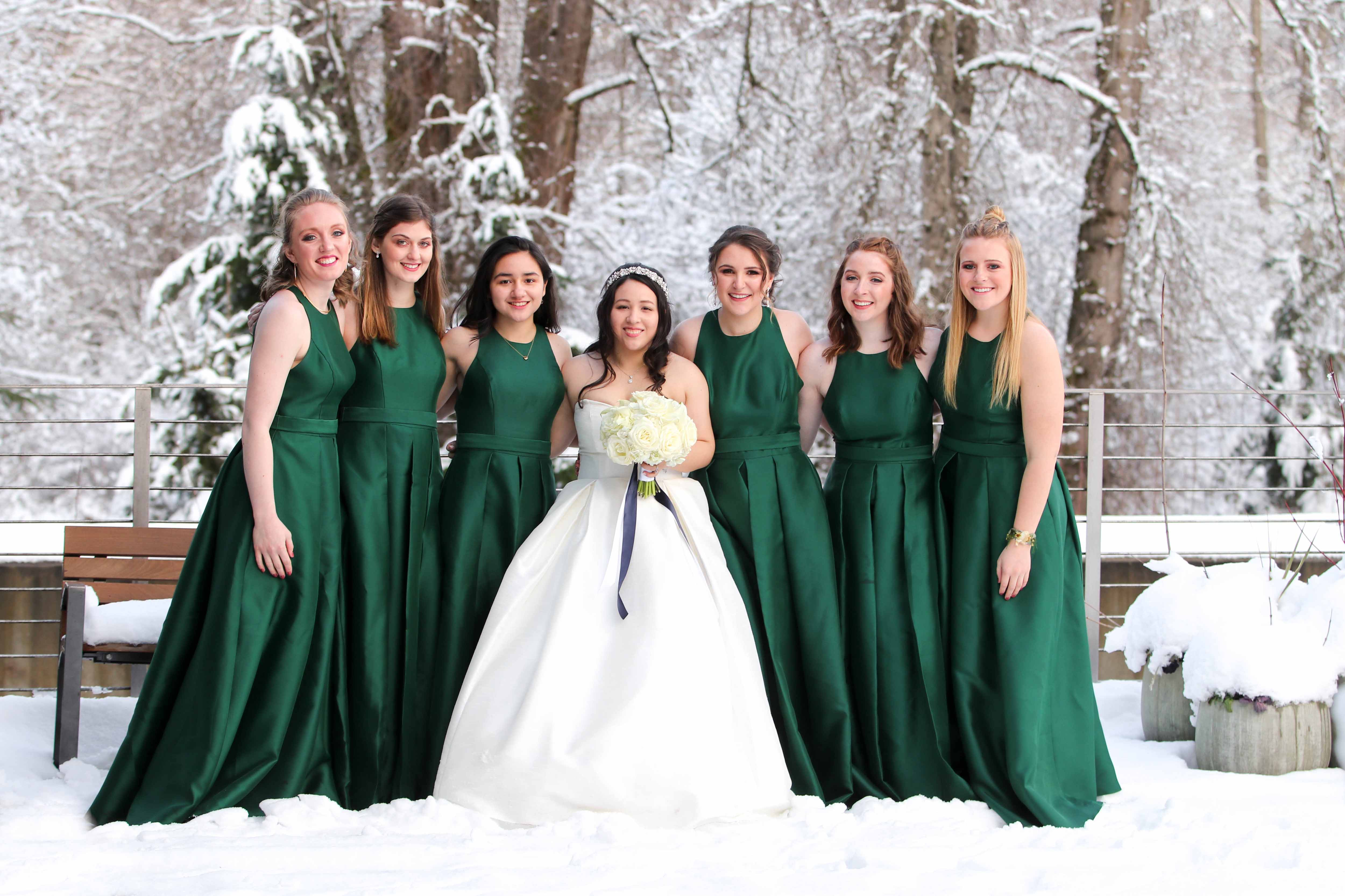 bride and bridesmaids in emerald green dresses pose in the snow