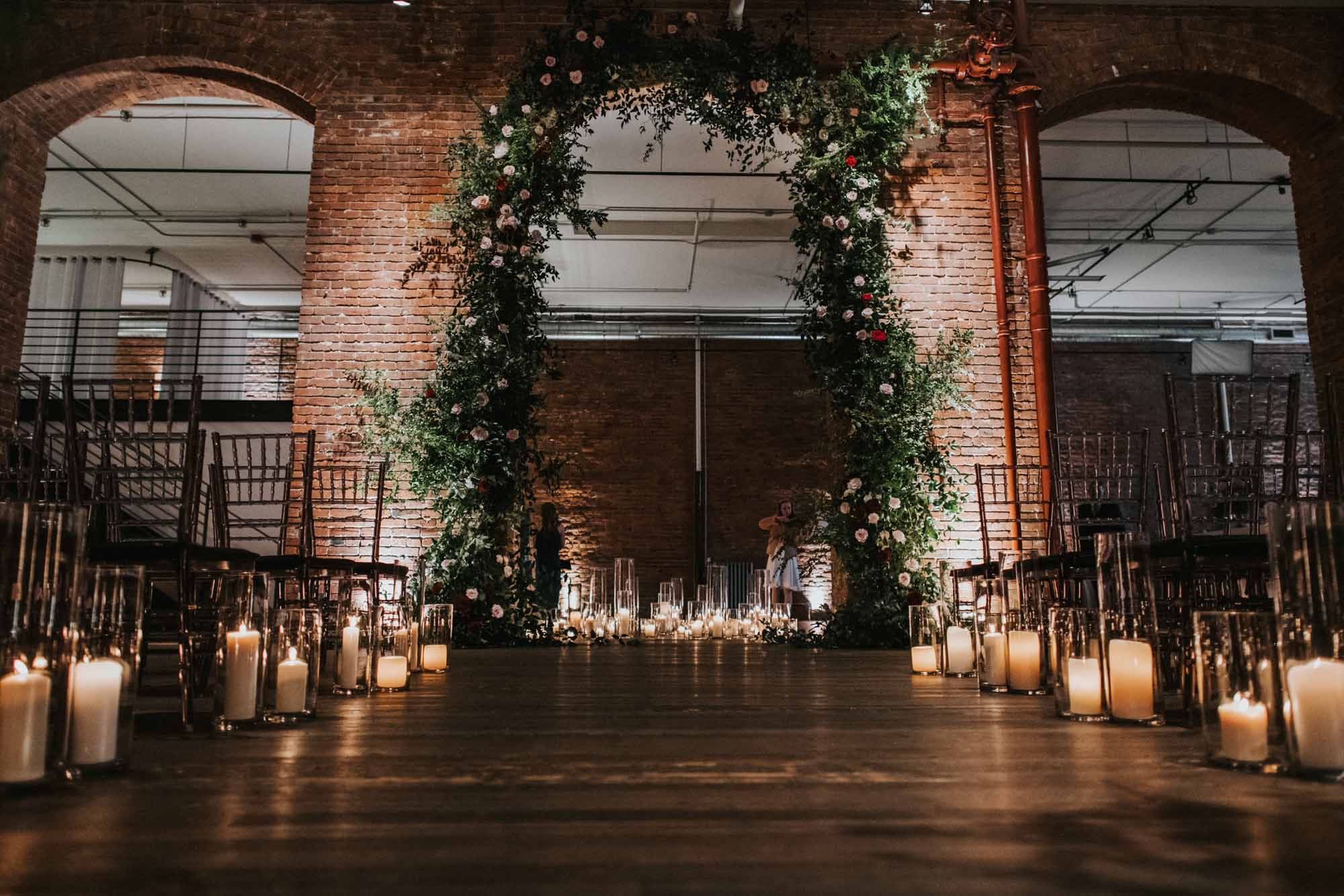 tall greenery arch in brick archway with hurricane candles