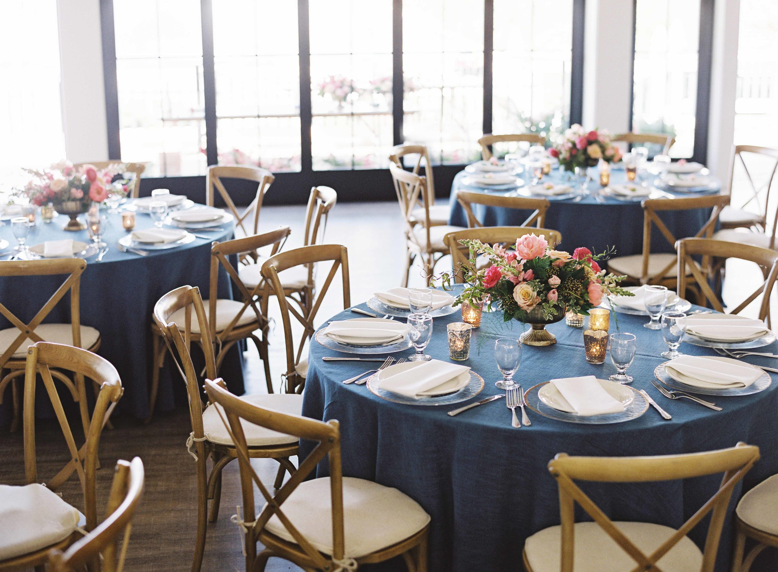 Vineyard chairs around round reception tables with blue linen and pink centerpiece - Seattle Wedding Flowers by Flora Nova Design; Hot pink and peach wedding at Roche Harbor Resort