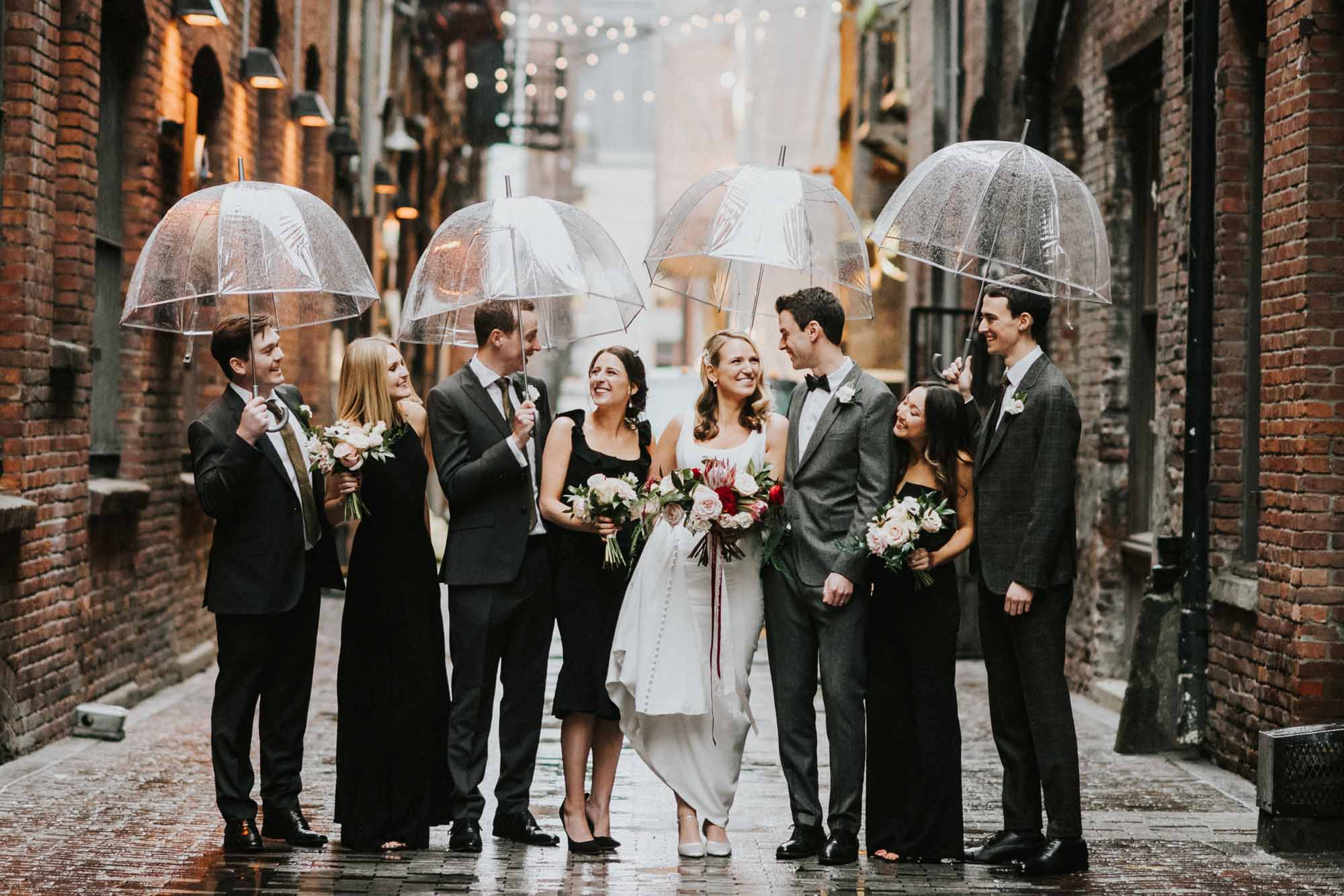 wedding party pose with umbrellas in brick alley