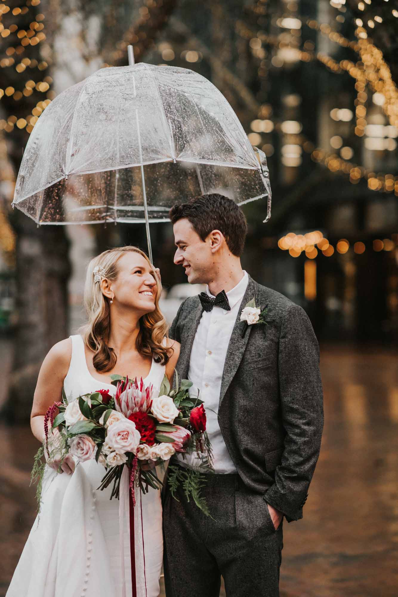 clear umbrella over bride and groom