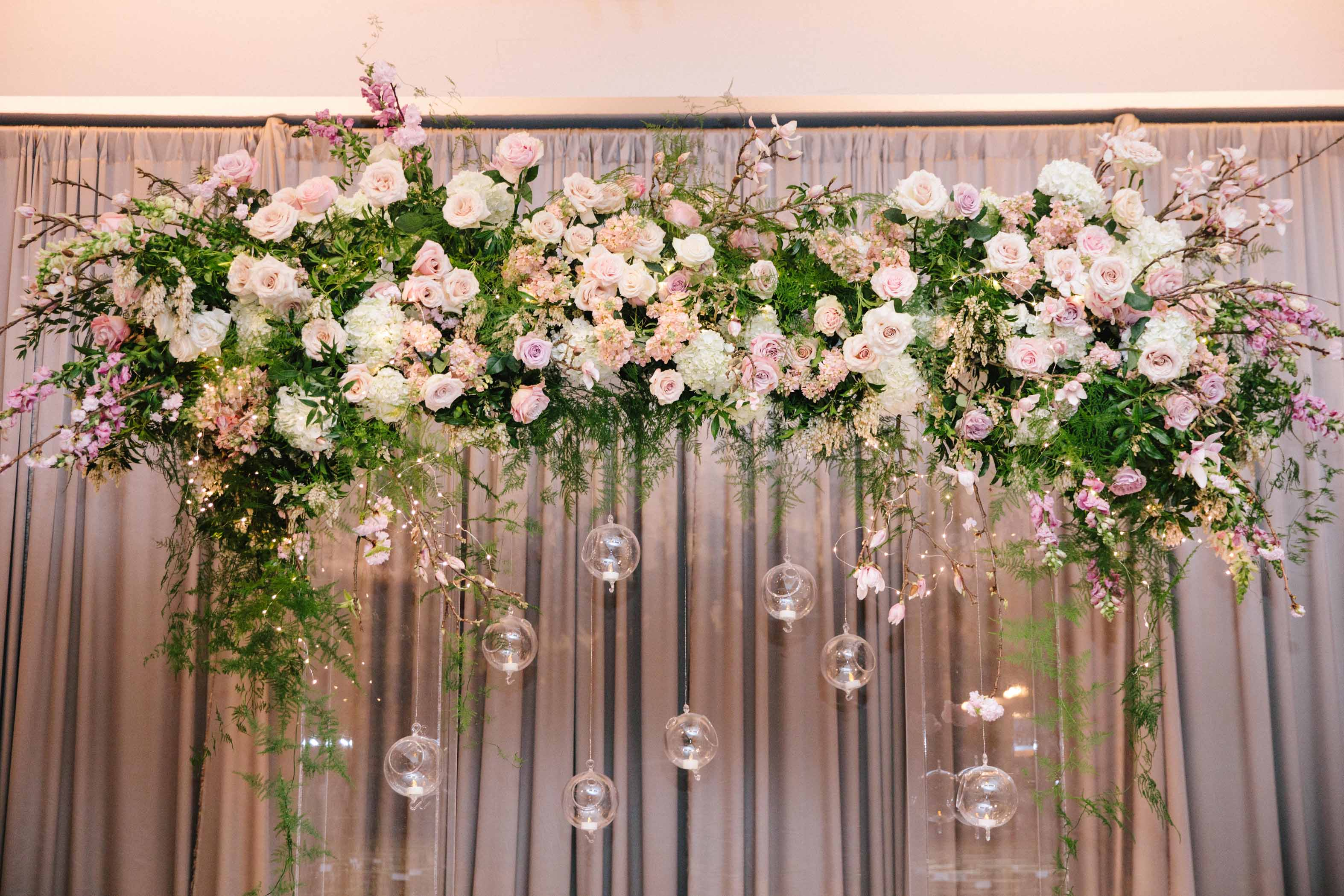 Wedding ceremony floral arch with hanging candles and vines