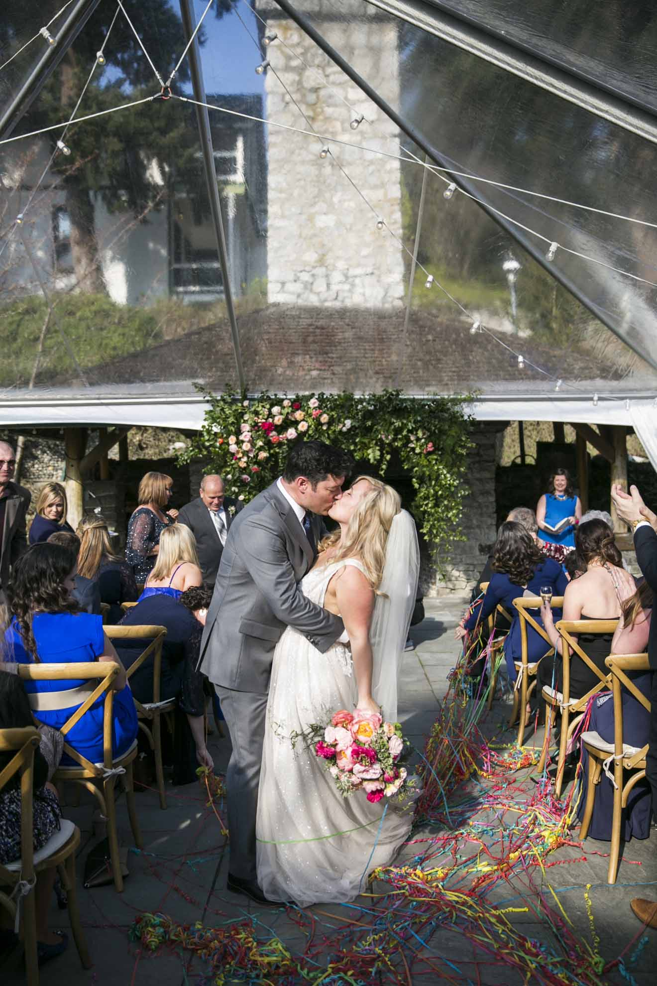 Bride and groom kiss at wedding ceremony under a clear tent; bride holding a hot pink and peach wedding bouquet - Seattle Wedding Flowers by Flora Nova Design; Hot pink and peach wedding at Roche Harbor Resort
