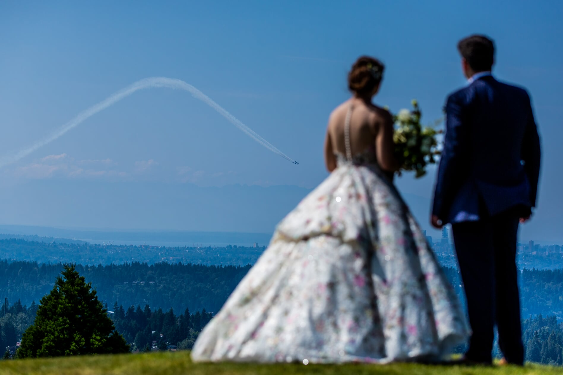 Bride and groom looking at airplane fling through blue sky