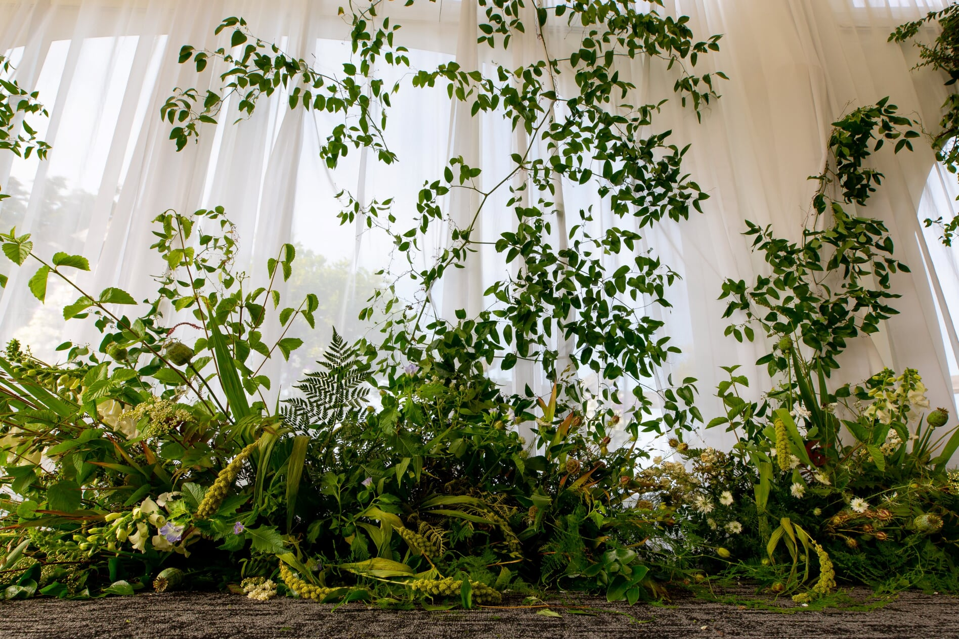 Greenery vines climbing walls of the tent at ceremony