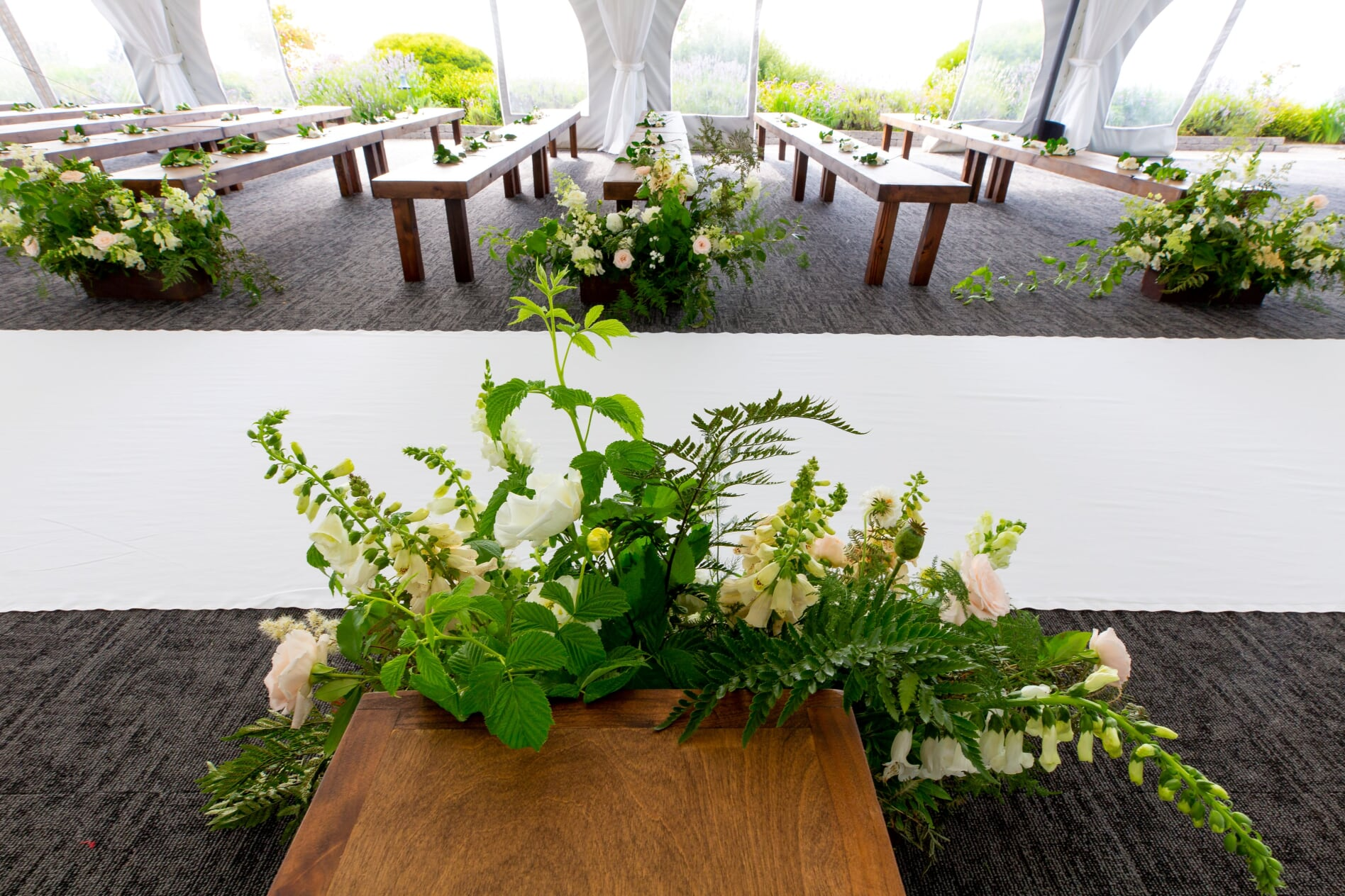 aisle flowers placed by wooden benches for ceremony
