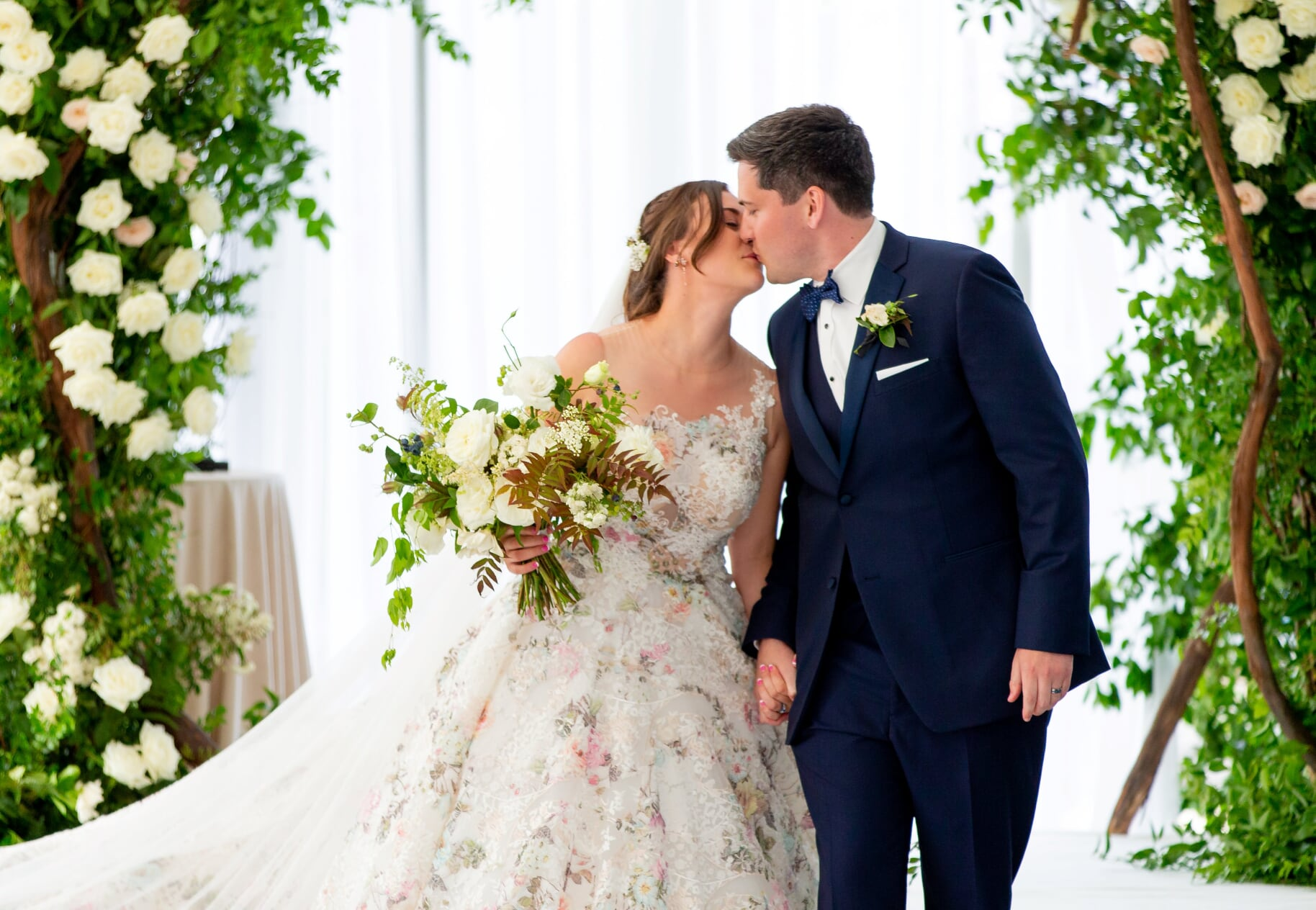 Groom and bride in floral wedding dress kiss in front of ceremony