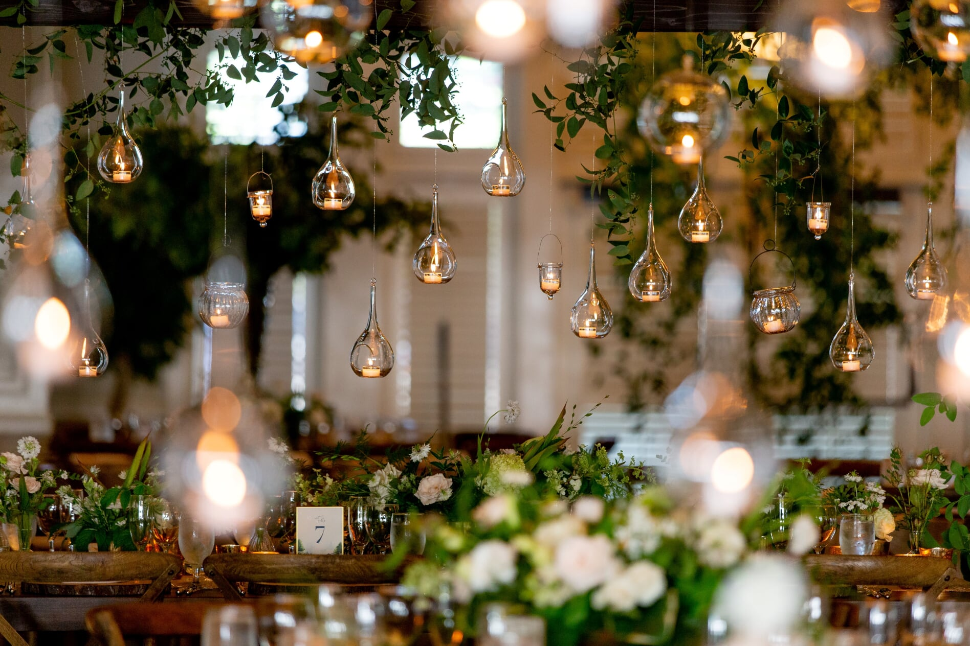 hanging votives over long tables with white centerpiece