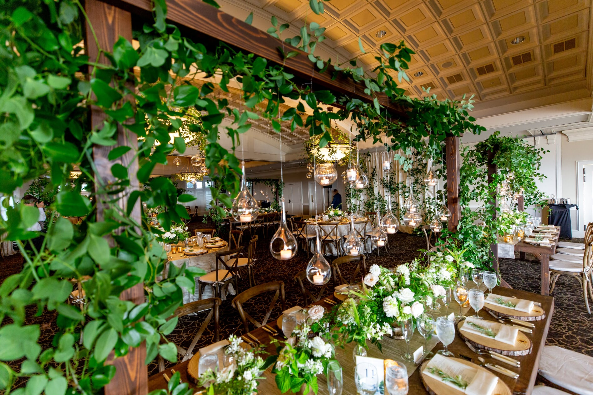 Midsummer Night's Dream Weddding Trellis over dining table hung with green vines and hanging candles