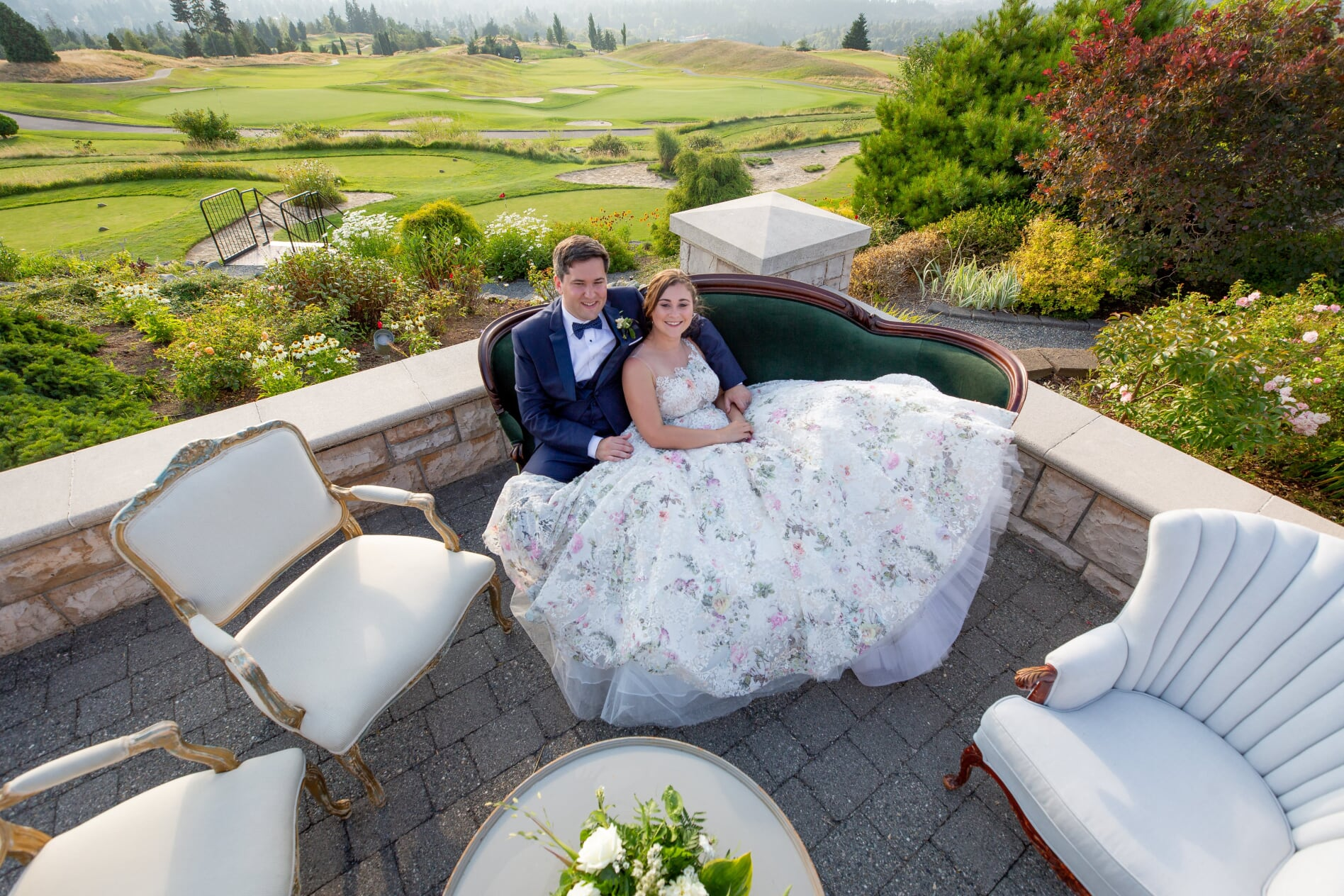 Groom and Bride in floral wedding dress sitting on velvet setee on veranda with gold course in background