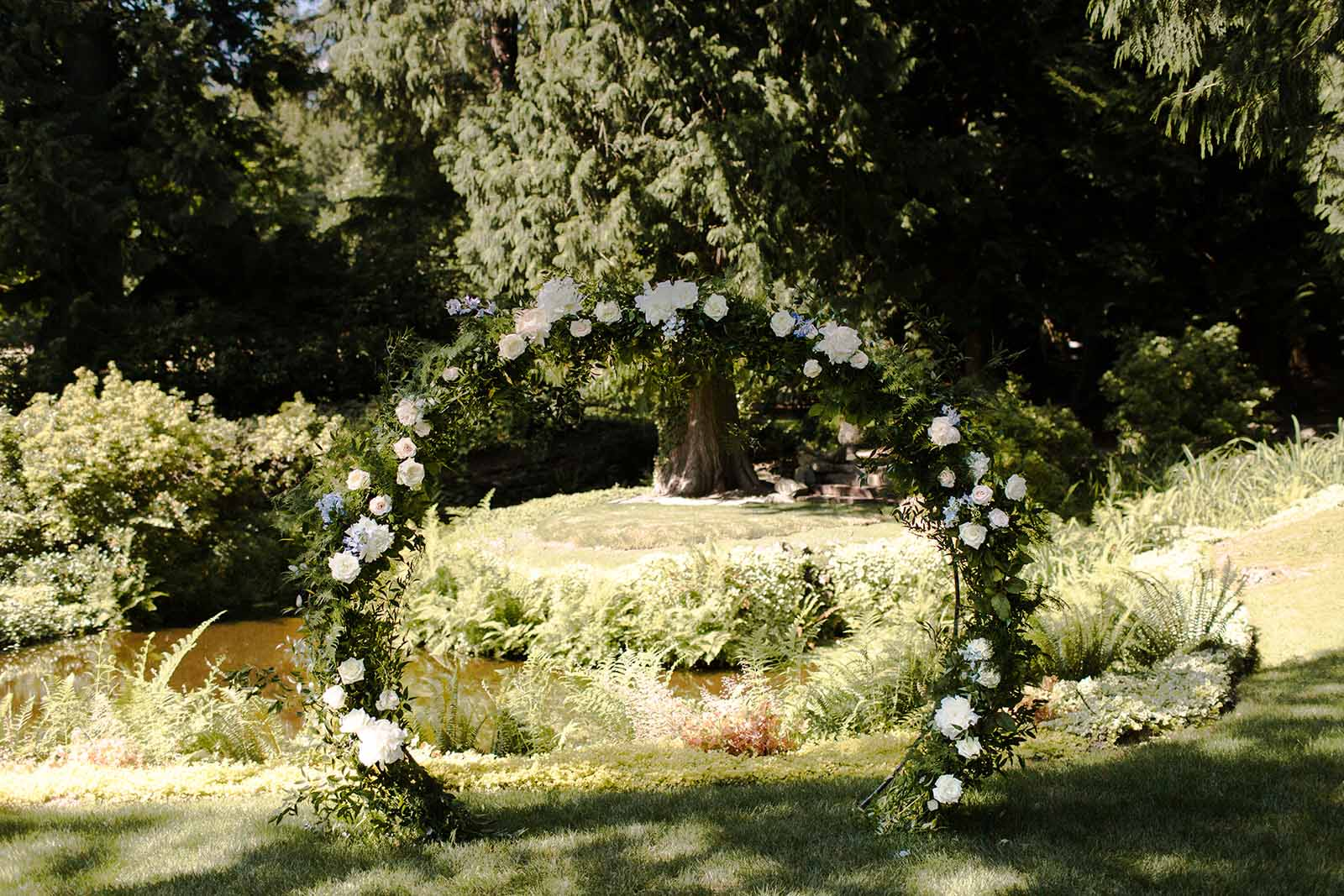 Circle arch under the trees at Chateau Lille, designed by Flora Nova Design, Seattle