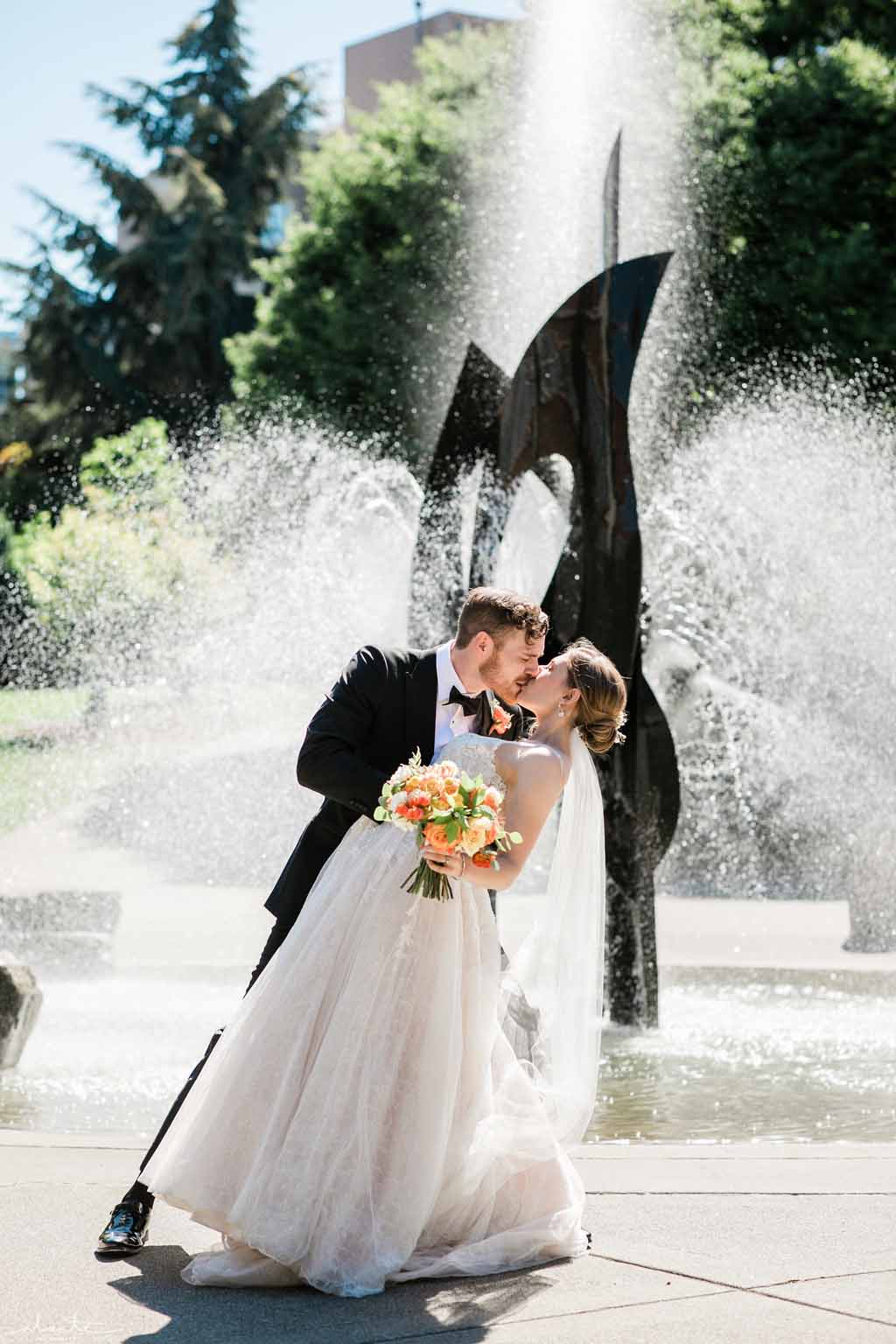 Bridal couple kissing their sunny summer wedding day in Seattle