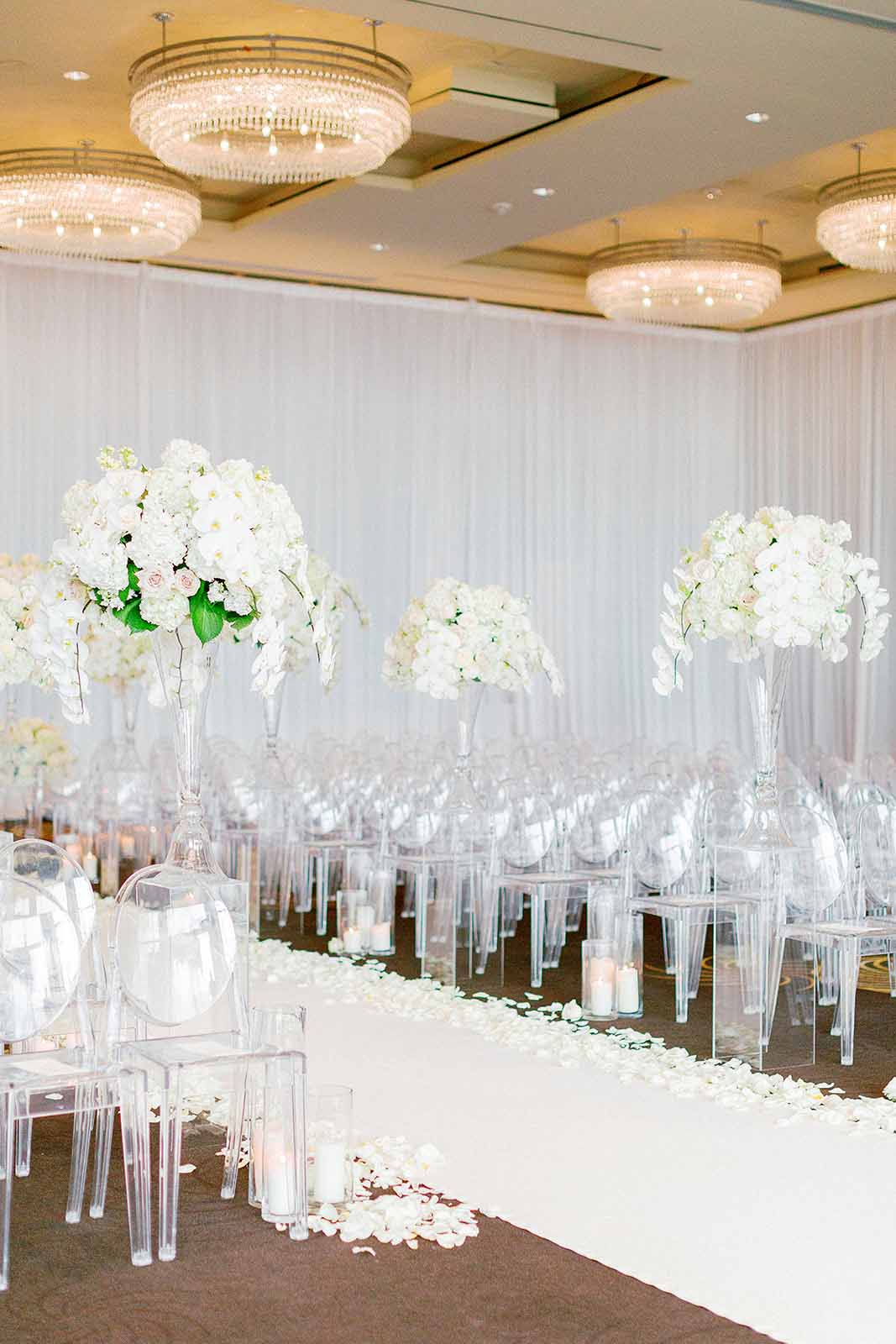 Ballroom wedding ceremony with all white floral arrangements lining the aisle of lucite ghost chairs