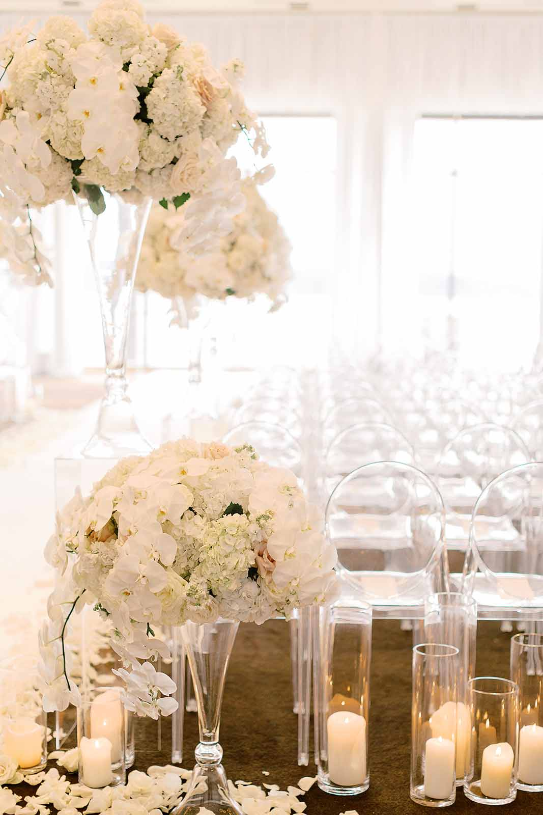 Aisle entrance to a formal Four Seasons wedding with tall white floral arrangements on crystal vases sit on a bed of rose petals and candles | Flora Nova Design Seattle
