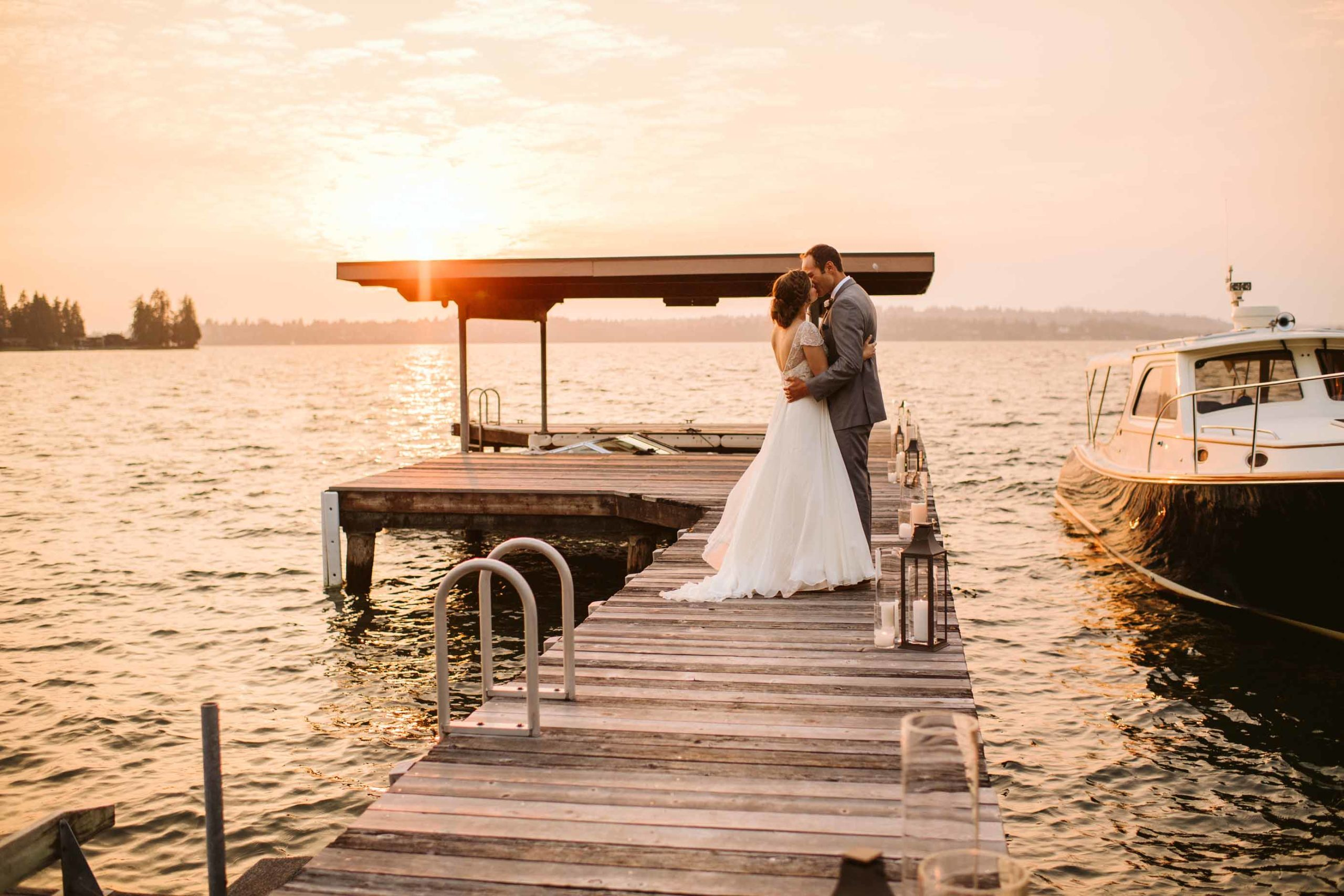 Sunset wedding portrait bride and groom kissing on a dock on Lake Washington