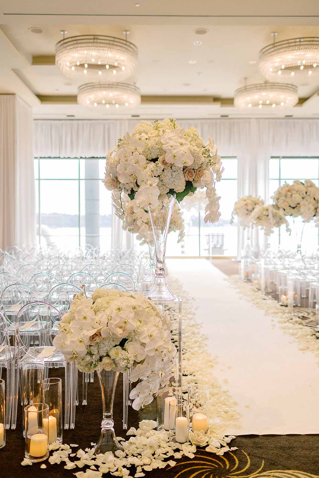 Ceremony aisle lined with white rose petals and candles, aisle entrance with elevated white tall floral for a formal Four Seasons Seattle wedding ceremony | Flora Nova Design