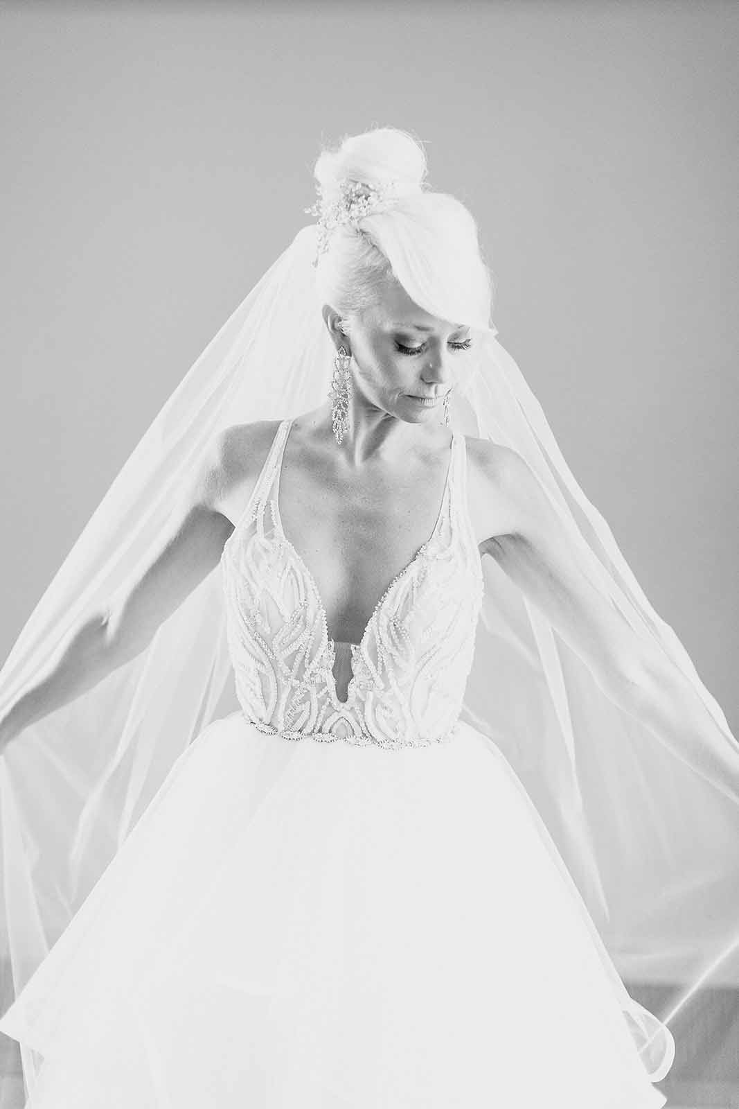 Formal black and white bridal photo in her full skirted fluffy ballgown style dress for a formal white ballroom wedding