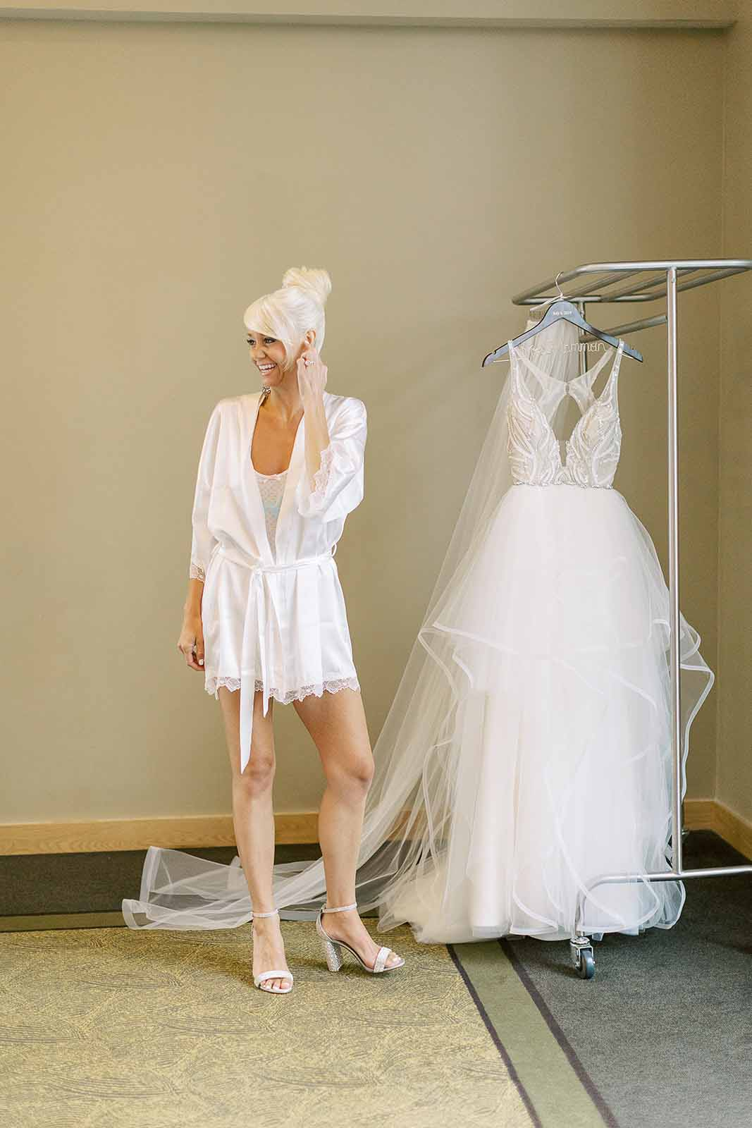 Bride in robe getting ready to put on her wedding dress for a formal ballroom wedding ceremony