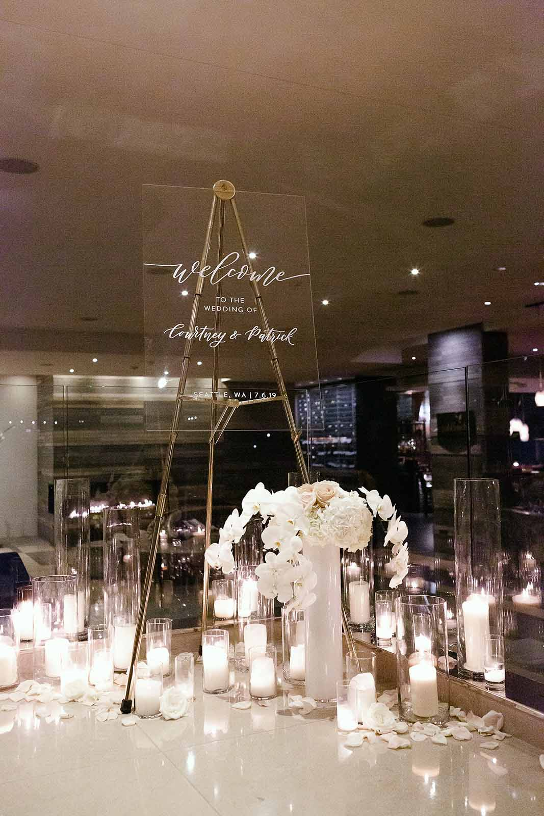 Candles line the staircase with a custom lucite sign and white floral welcomes guests to the ceremony space for a formal ballroom wedding