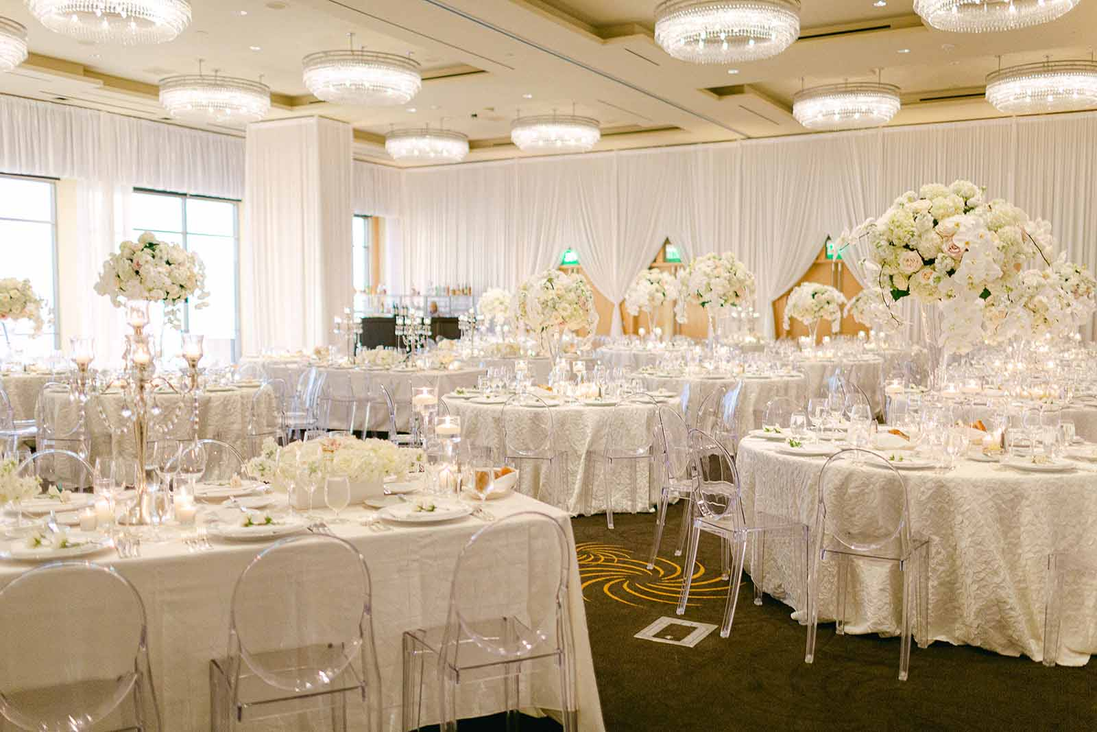 Formal reception in a white draped ballroom at the Four Seasons Seattle for a summer white orchid wedding with tall floral centerpieces and Lucite ghost chairs | Flora Nova Design