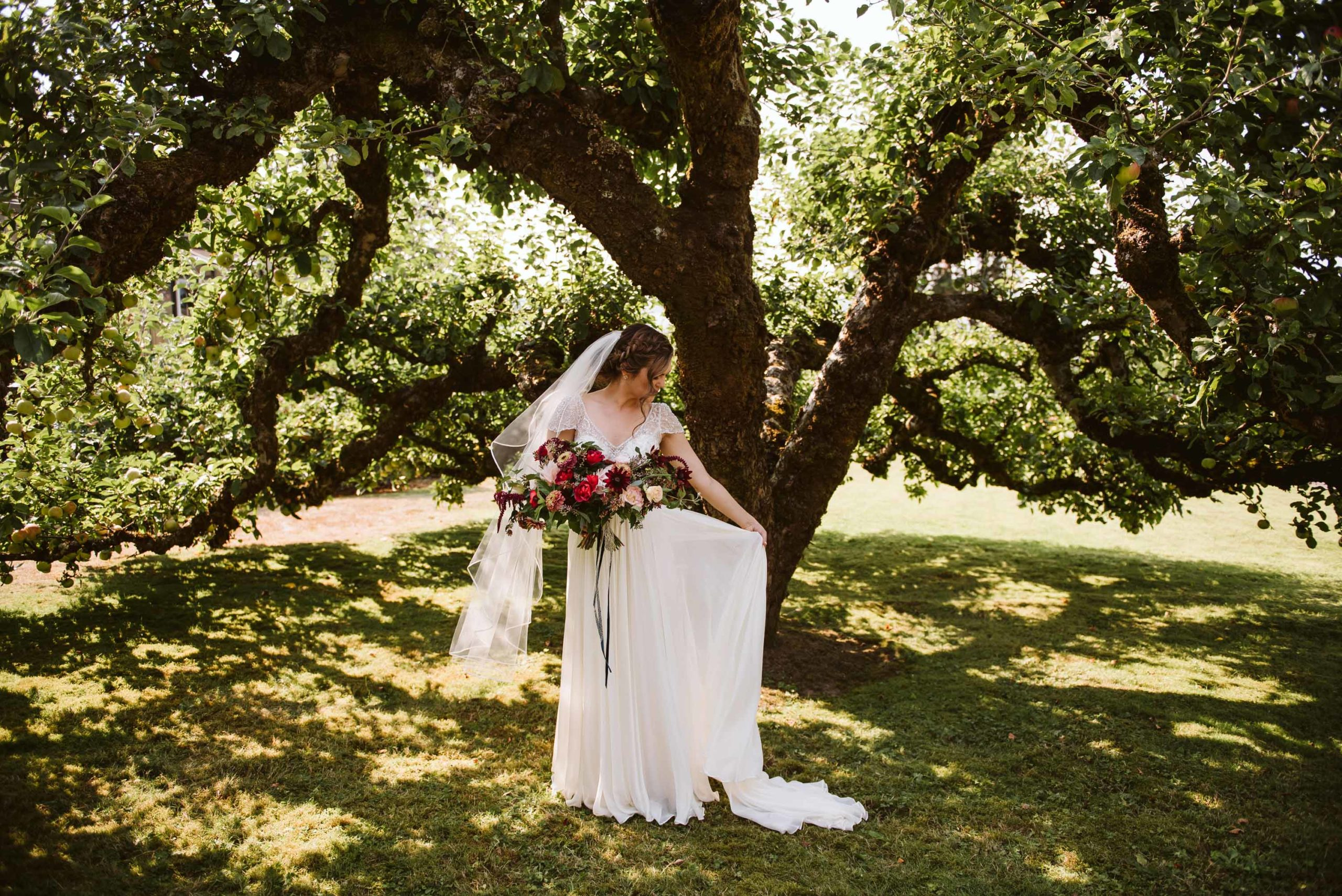 Bride in her family's orchard where they held an intimate summer wedding. | Flora Nova Design