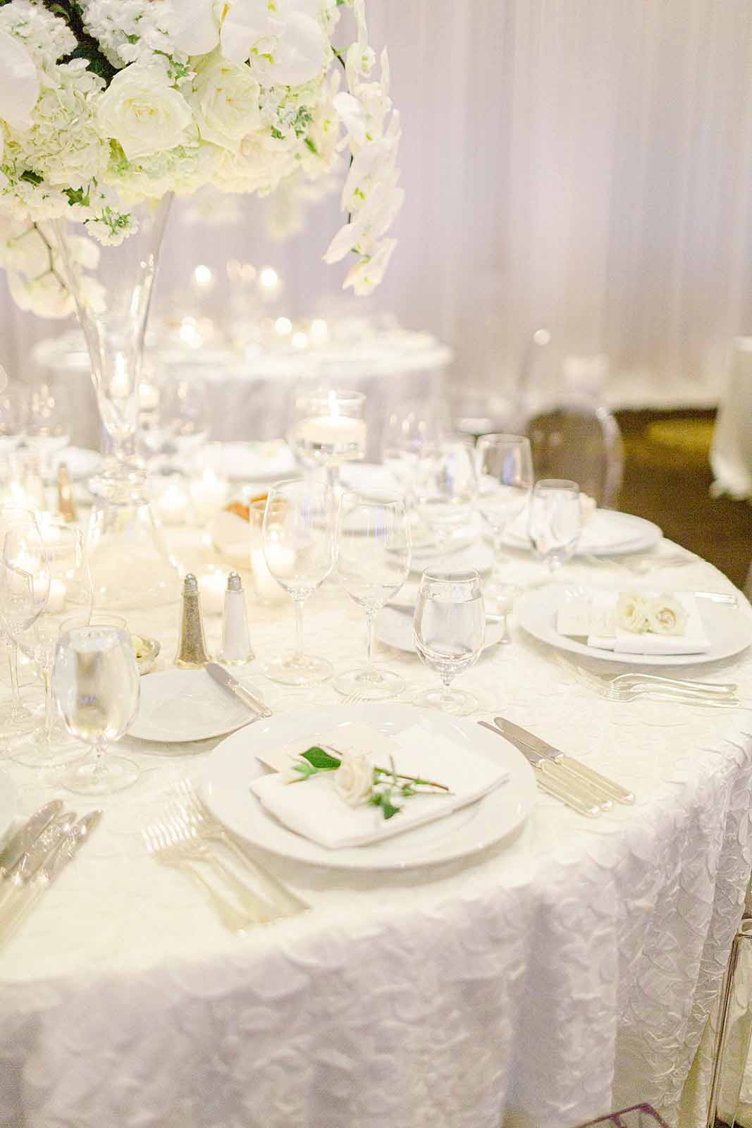 Round reception table in all white with a elevated rose and orchid floral centerpiece and floating candles designed by Flora Nova Design Seattle