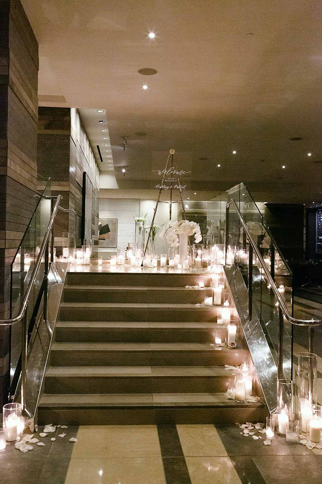Four Seasons Seattle staircase lined with white hurricane candles and floral leading to the ballroom wedding | Flora Nova Design