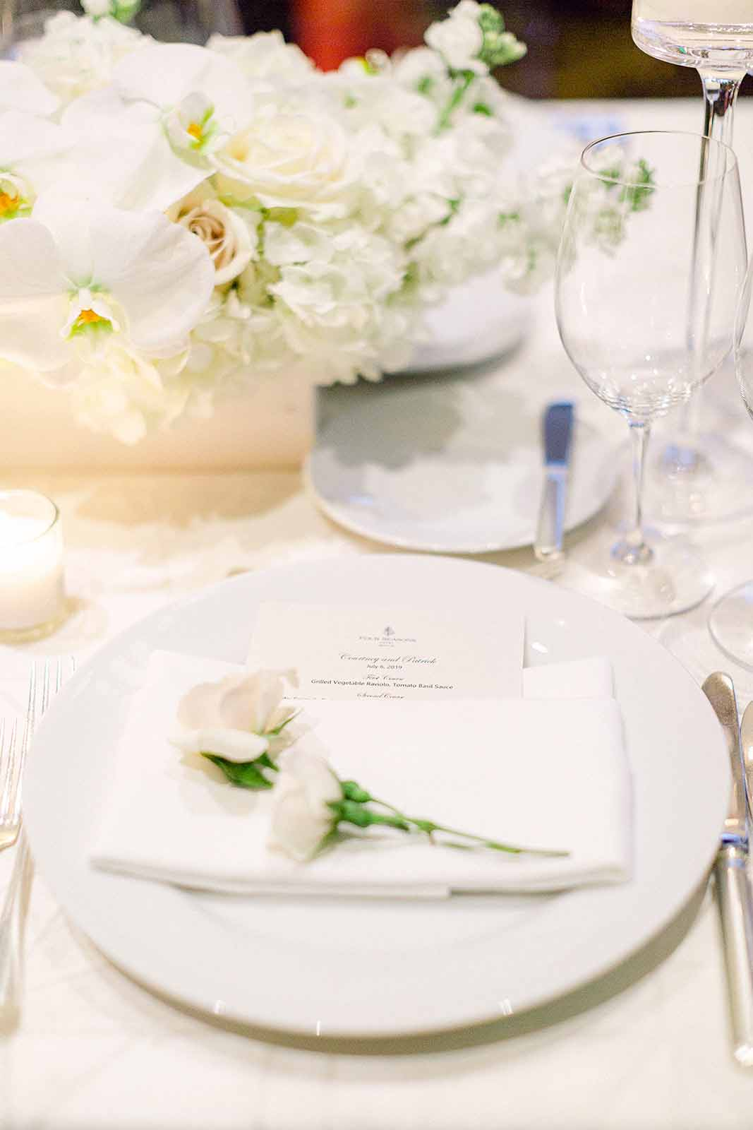 Detailed place setting with white rose at each place setting with low floral orchid centerpieces