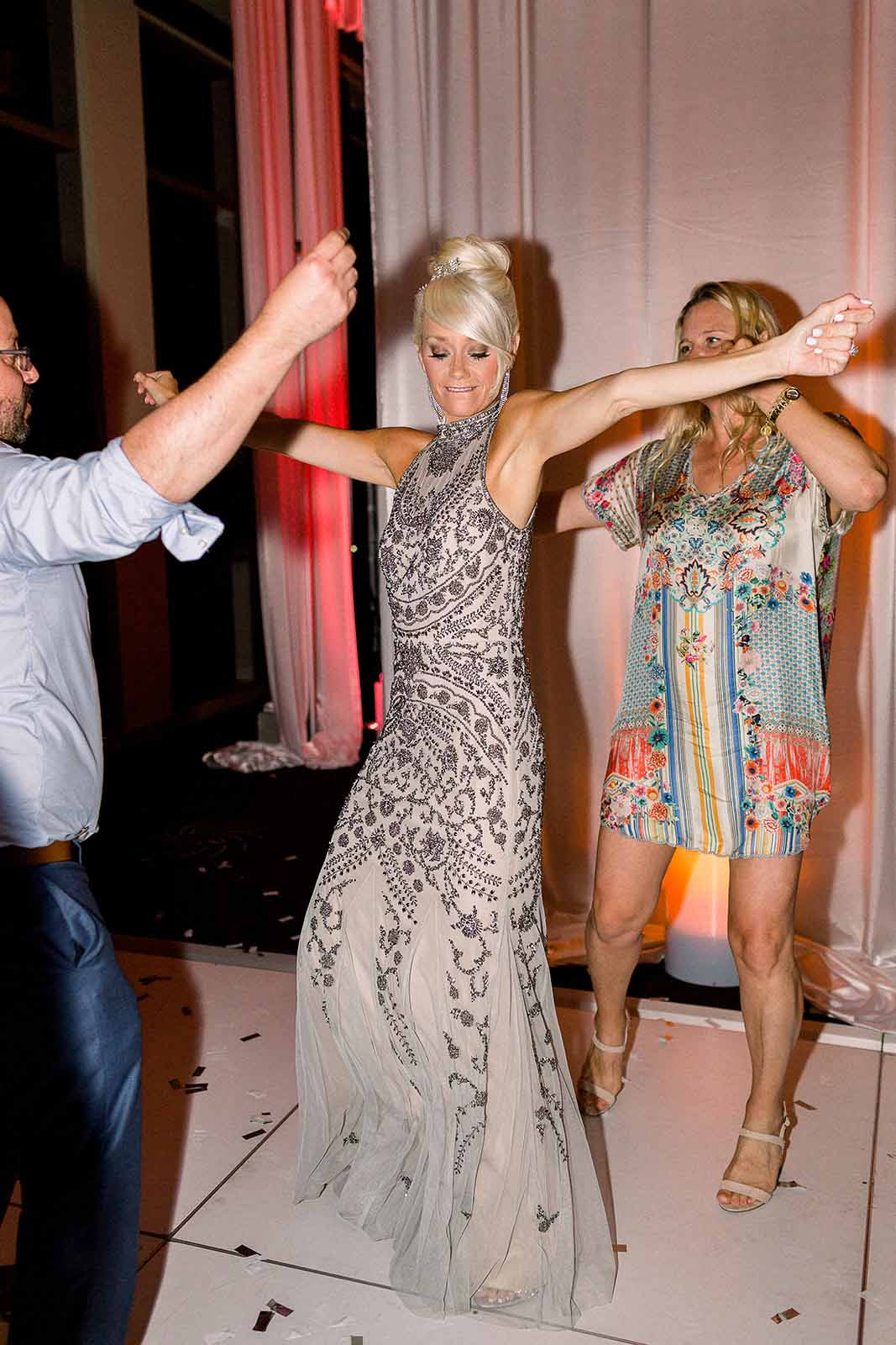 Guests dance with the bride on the dance floor at a formal wedding reception