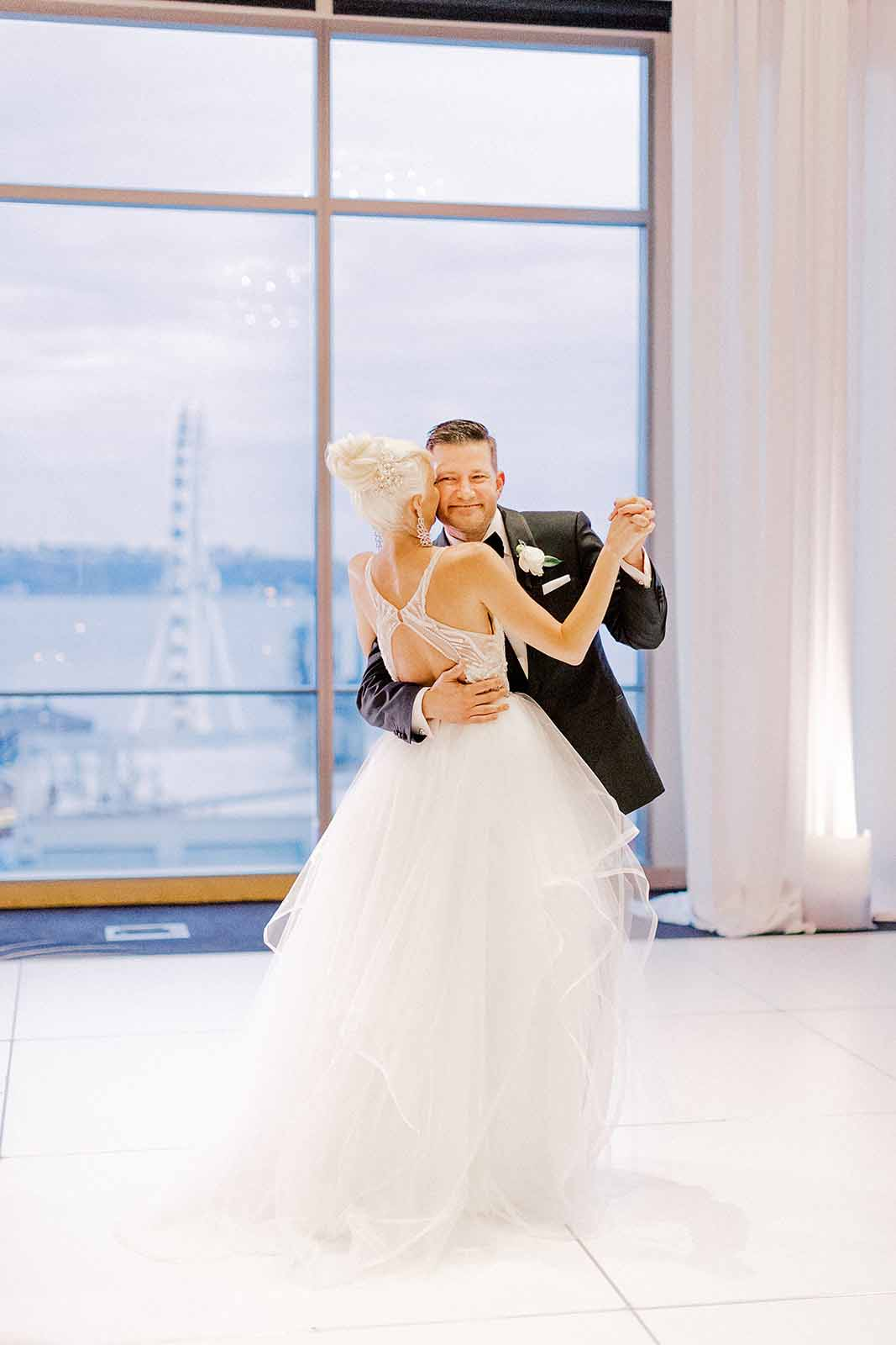Bride and groom dancing in the Four Seasons Ballroom Seattle during their summer white orchid wedding