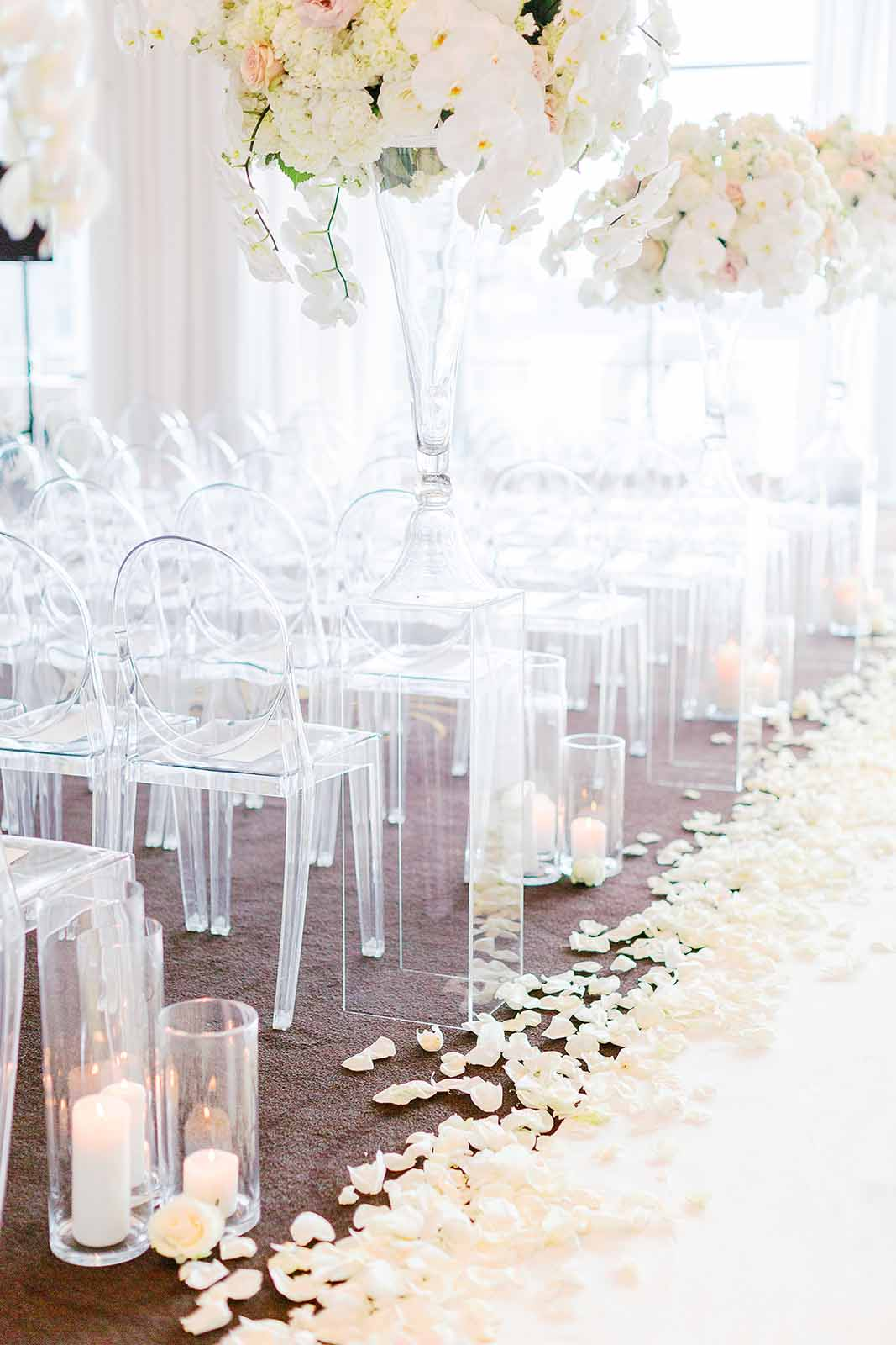 Ballroom wedding ceremony with all white floral arrangements lining the aisle of lucite ghost chairs with aisle runner and white roses petals Flora Nova Design Seattle