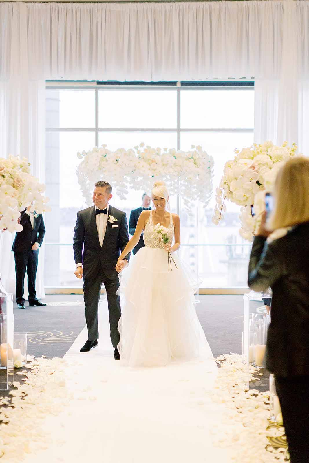 Bride and Groom holding hands in front of white orchid arch on a aisle runner lined with rose petals during their formal ballroom ceremony | Flora Nova Design Seattle