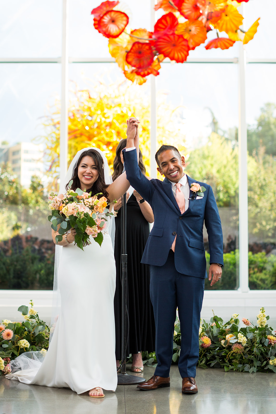 Bride and groom just married at their fall navy blue and burnt orange wedding at Chihuly | Flora Nova Design