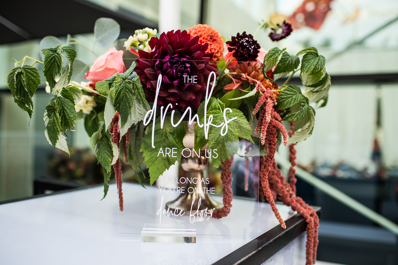 Low compote arrangement with dahlias with a lucite drinks menu in front of it for a fall wedding reception | Flora Nova Design Seattle