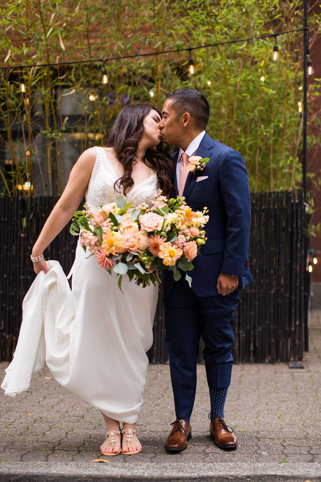 Bride and groom posing with a coral, peach and grey bridal bouquet for an Autumn Wedding at Chihuly Gardens and Glass | Flora Nova Design