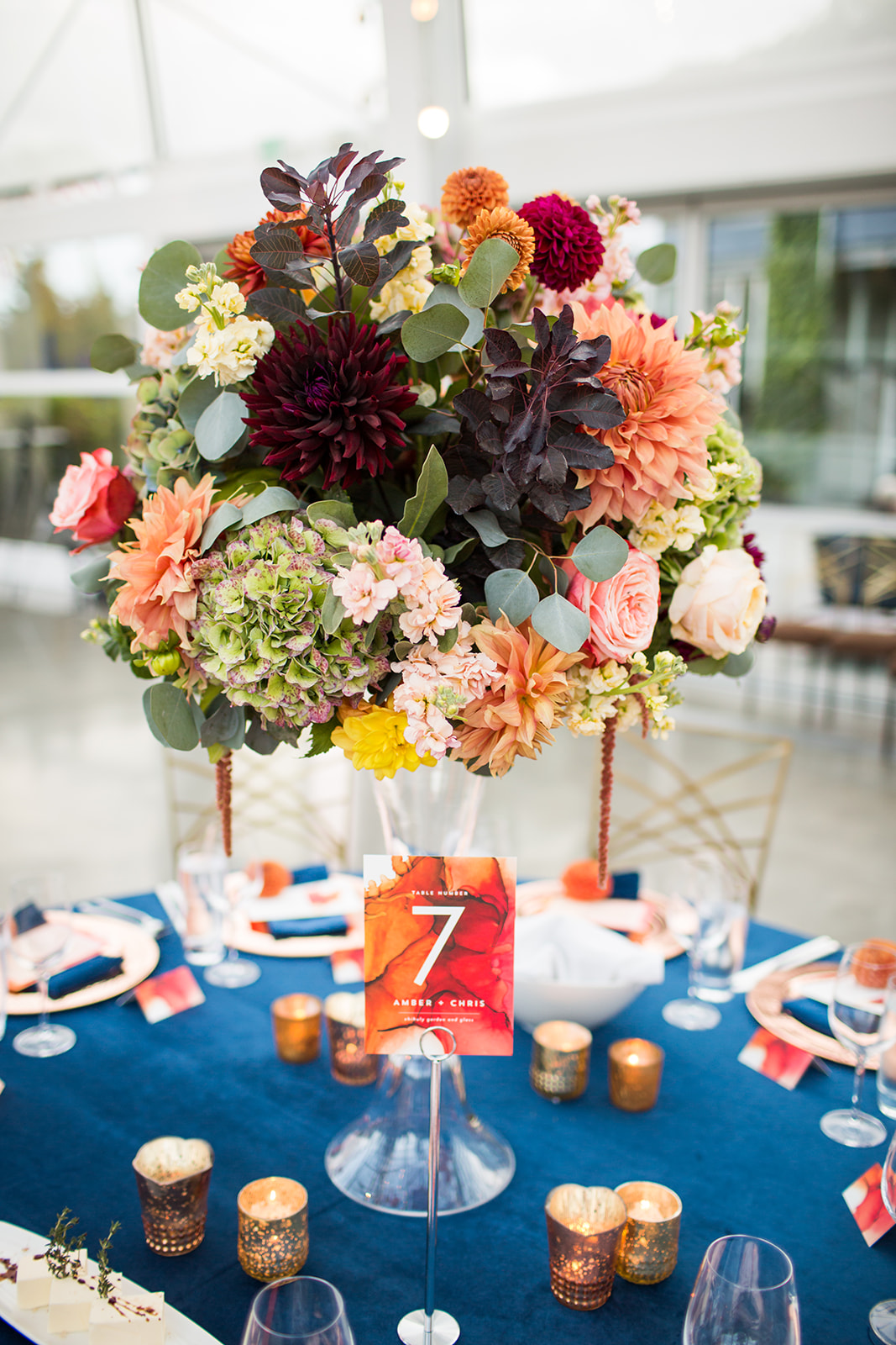Tall centerpiece with fall flowers in burgundy, burnt orange, and grey colors on navy blue velvet linens | Flora Nova Design Seattle