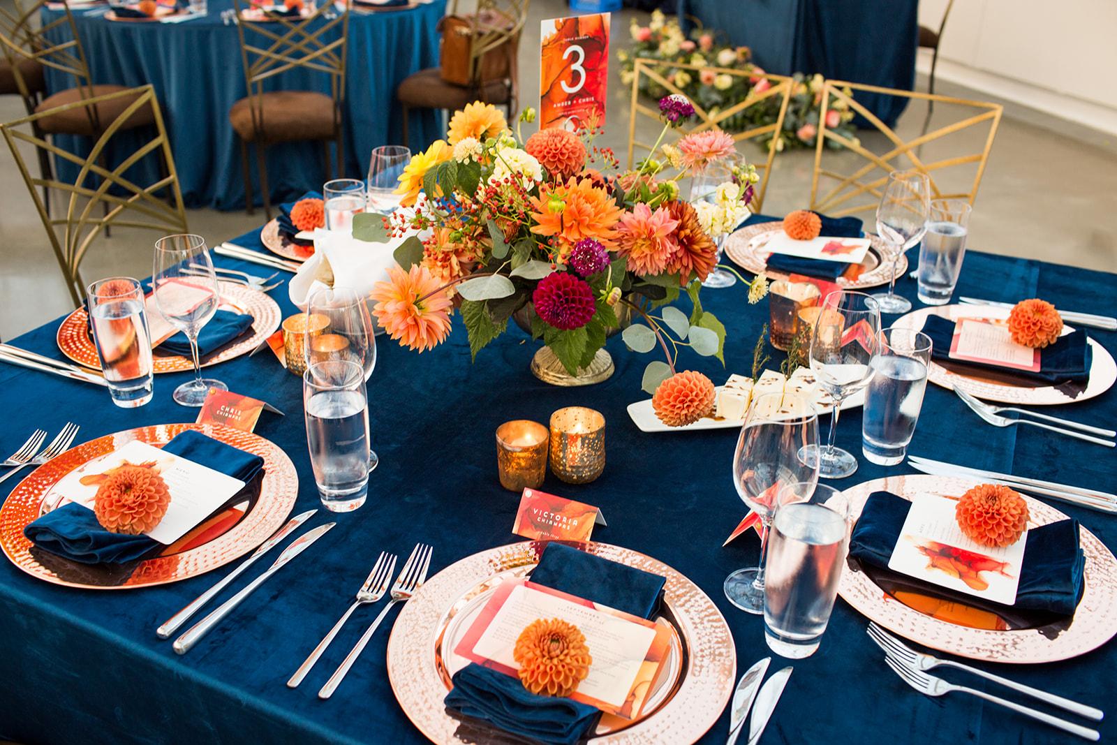 Low centerpiece on navy blue velvet linen with burnt orange, red, and peach dahlias, for a fall wedding reception | Flora Nova Design