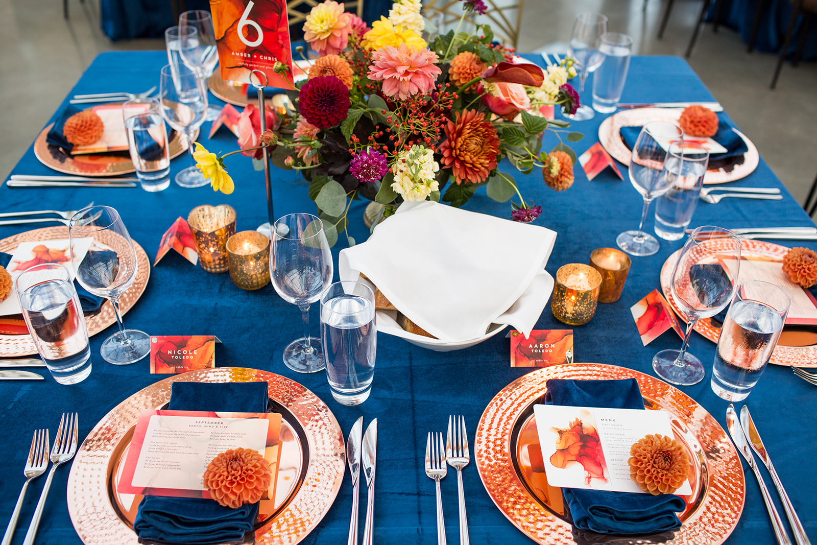 Autumn wedding table setting with low compote floral in rust, burnt orange, and peach dahlias with rose gold charges and navy blue linens | Flora Nova Design Seattle