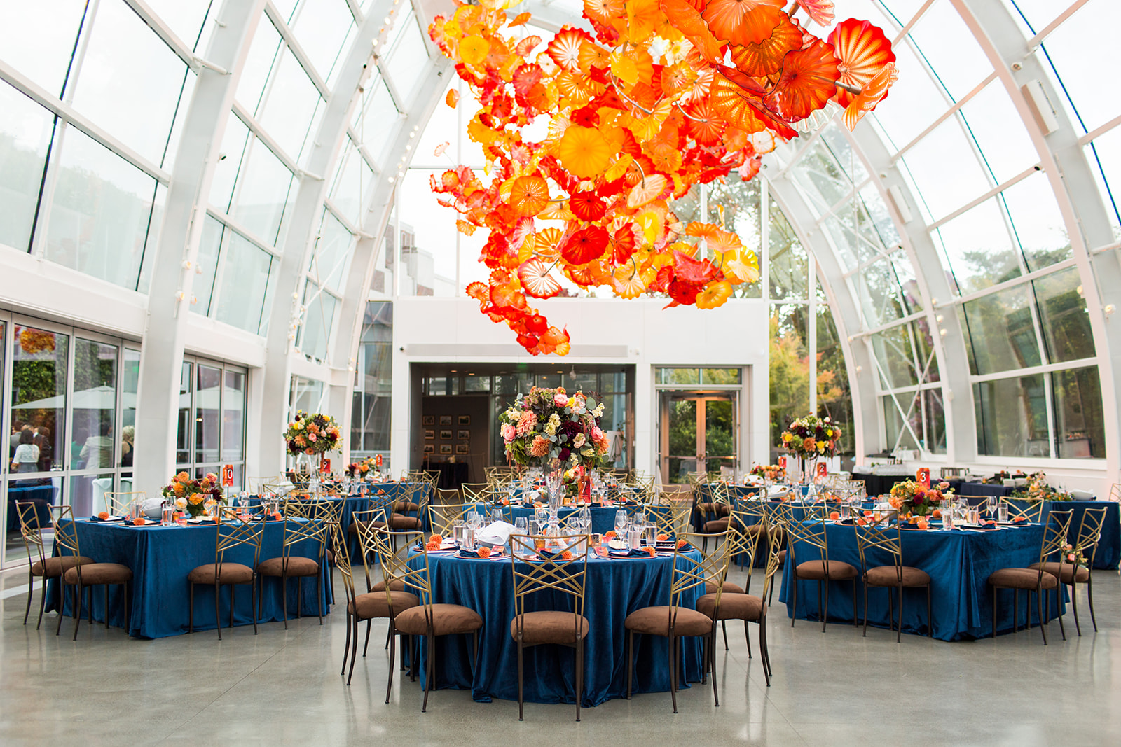 Fall navy blue and burnt orange wedding reception in Chihuly glasshouse with navy velvet linens and tall peach and orange centerpieces designed by Flora Nova Design Seattle
